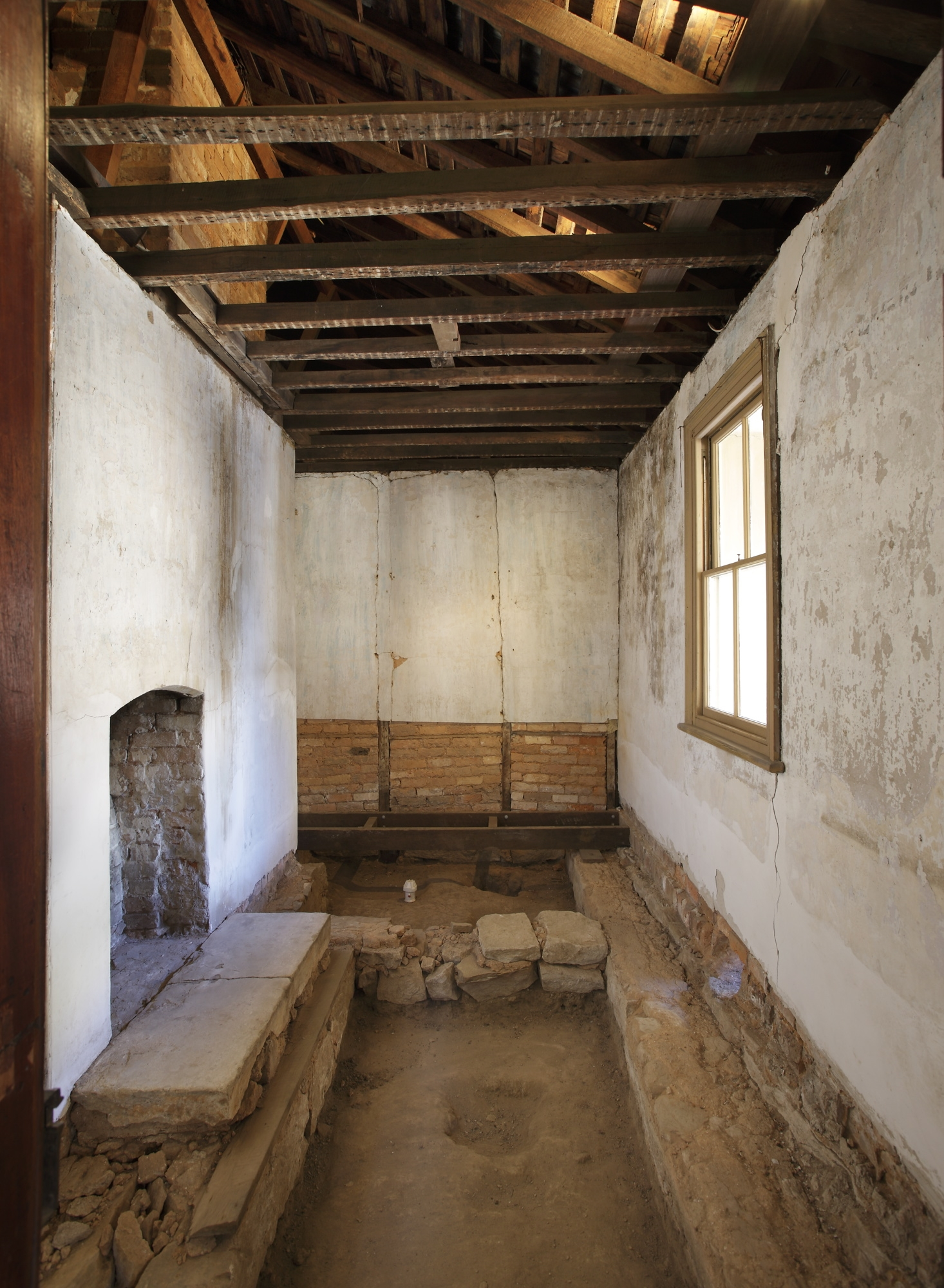 View of unrefurbished room showing excavated floorboards.