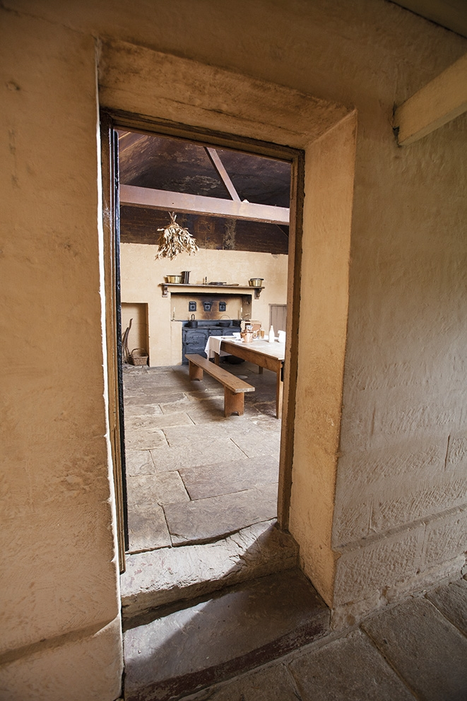Looking through open doorway into flagstone floored kitchen.