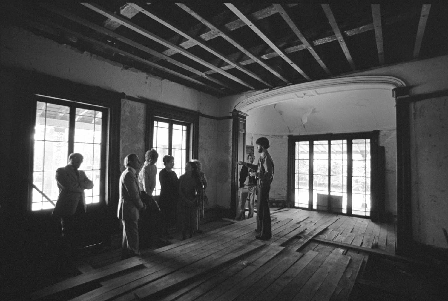 people inspecting room of old house with loose floorboards underfoot, large french doors, a large archway and exposed ceiling above.