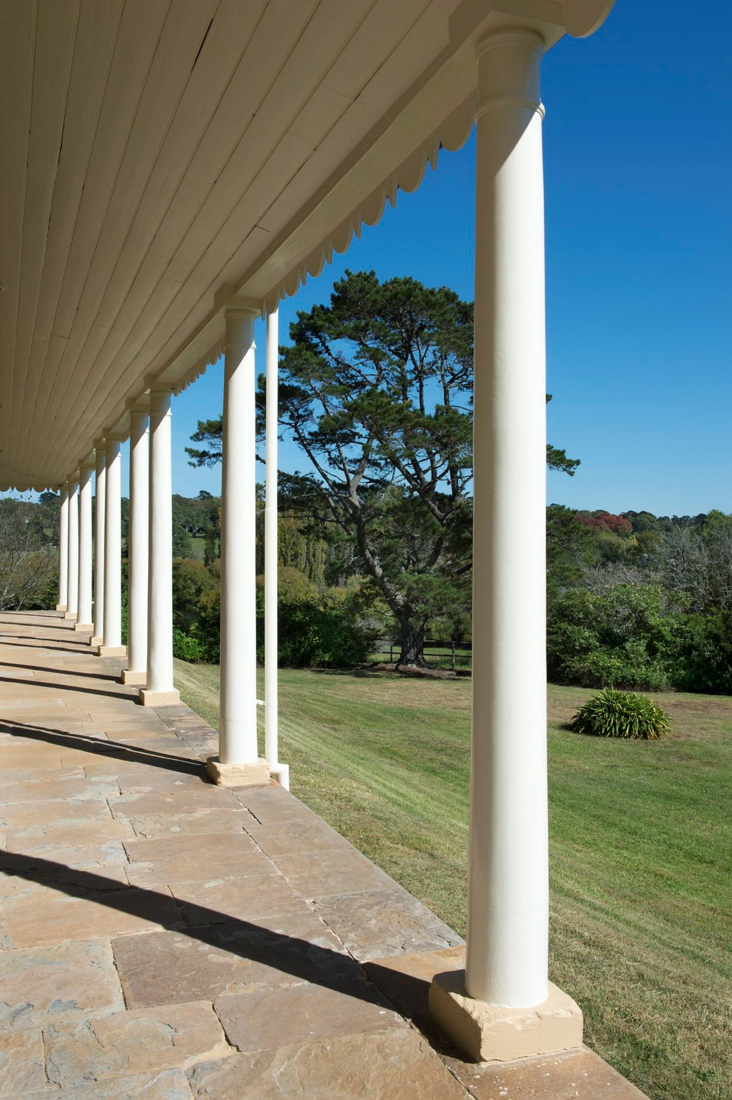 White columned verandah at throsby park with pasture and bushlands in the distance.