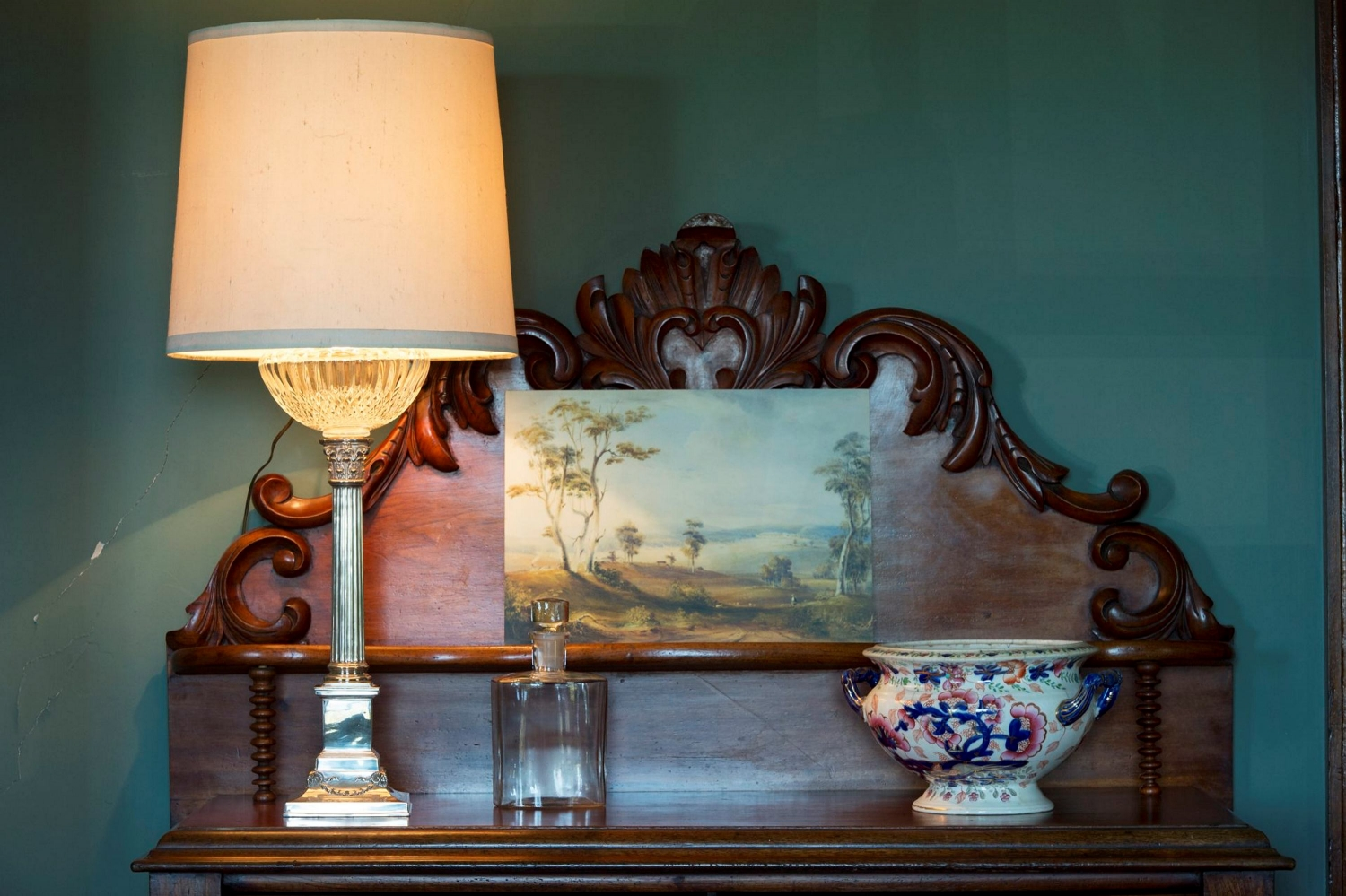 The shelf of a chiffonier with an old lampshade, painting and other ornaments against a green wall.