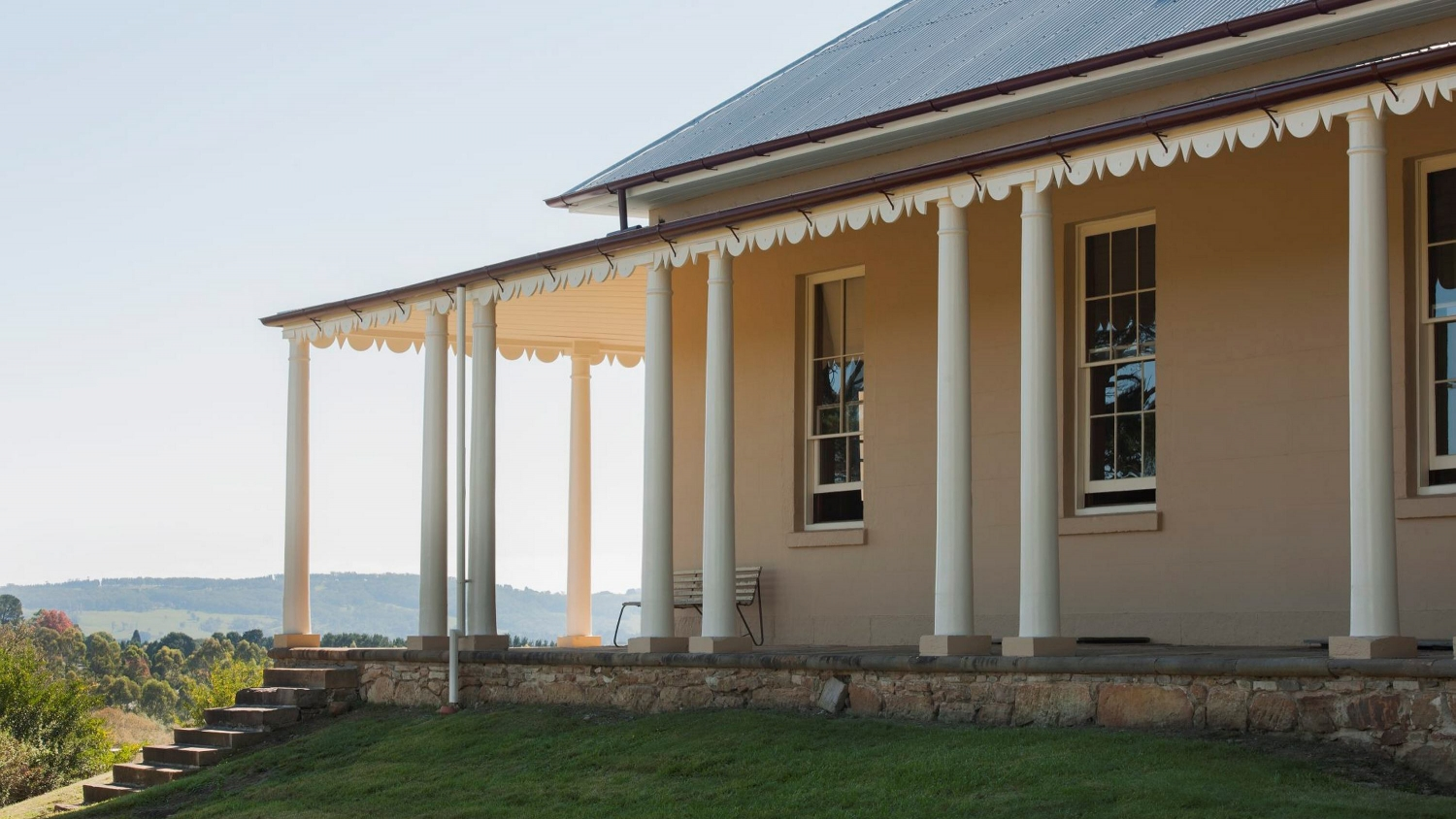 A house with wide verandah and white posts overlooks a grassy lawn and rolling hills in the distance