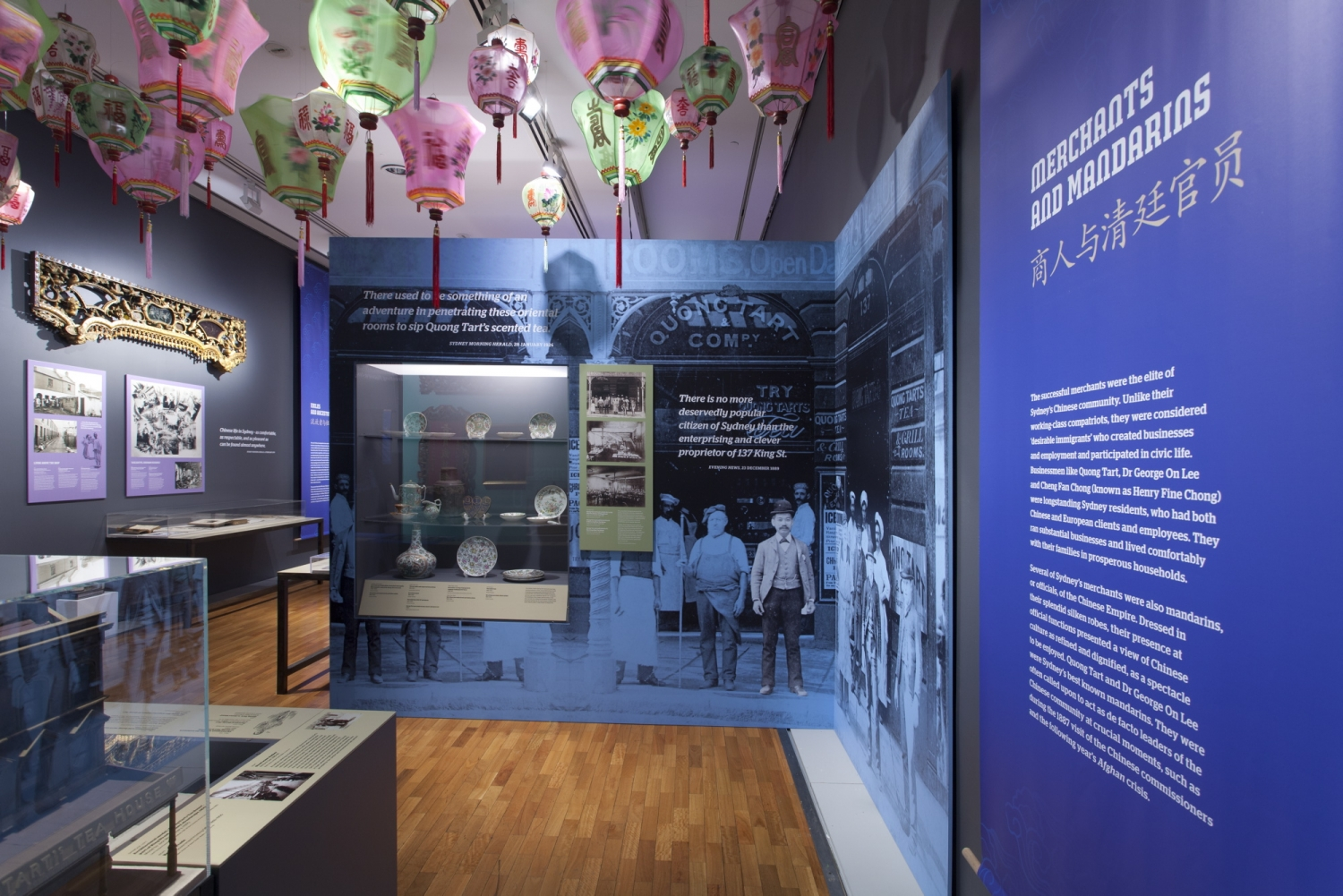 This is a photograph inside the exhibition showing a large black print on a blue background of people standing outside a tea house in Sydney. This supergraphic has a display case built into featuring ceramic objects and the graphic forms a a corner