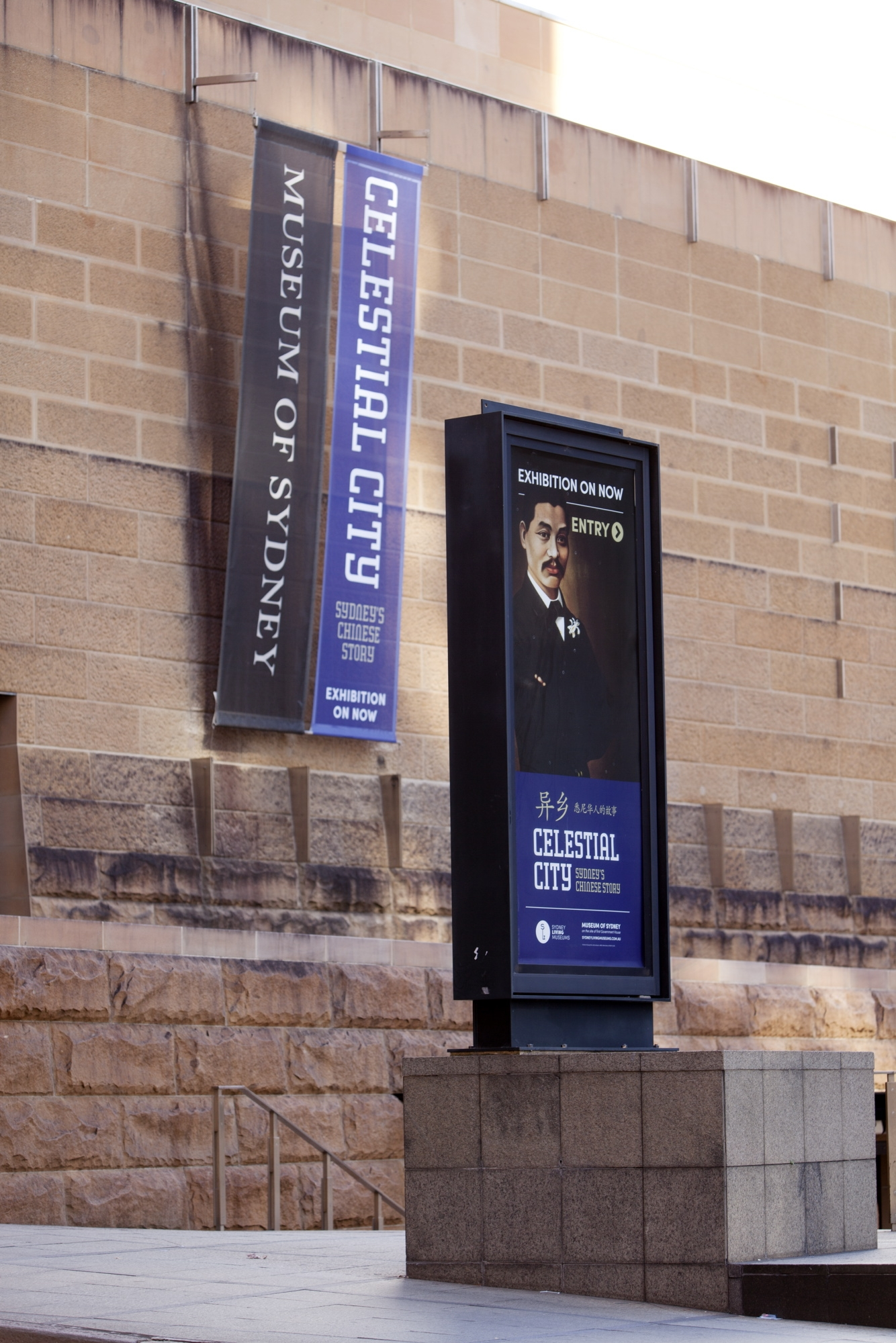 This is a photograph of a building banner advertising the Celestial City exhibition and a large scale poster featuring a portrait of Quong Tart
