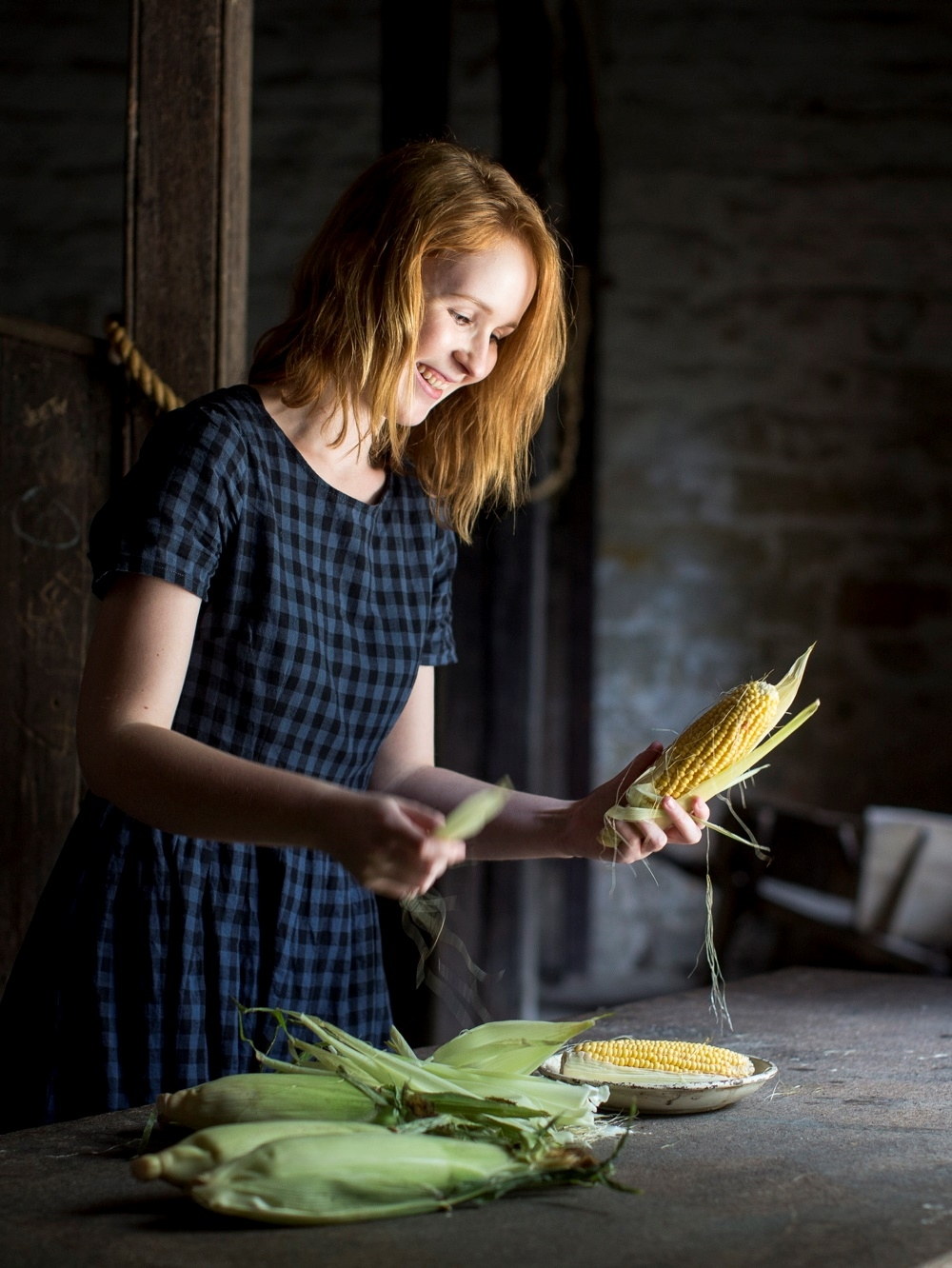 Photograph of a person peeling corn