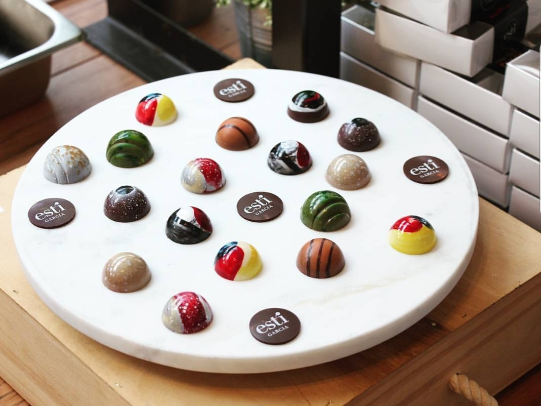 White circular platter with hand painted chocolates on it.