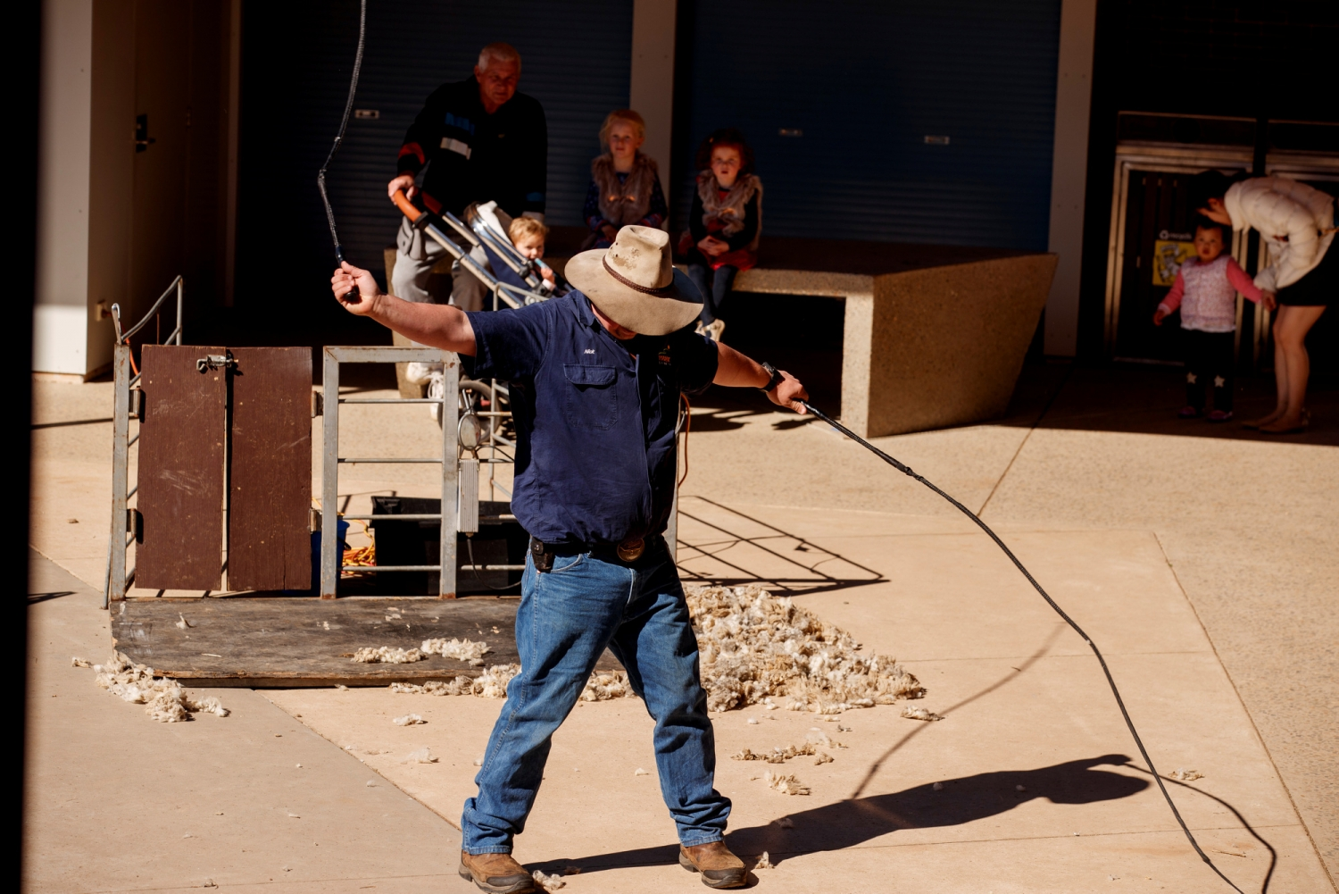 Man demonstrating stock whips using two at once, with lookers on.