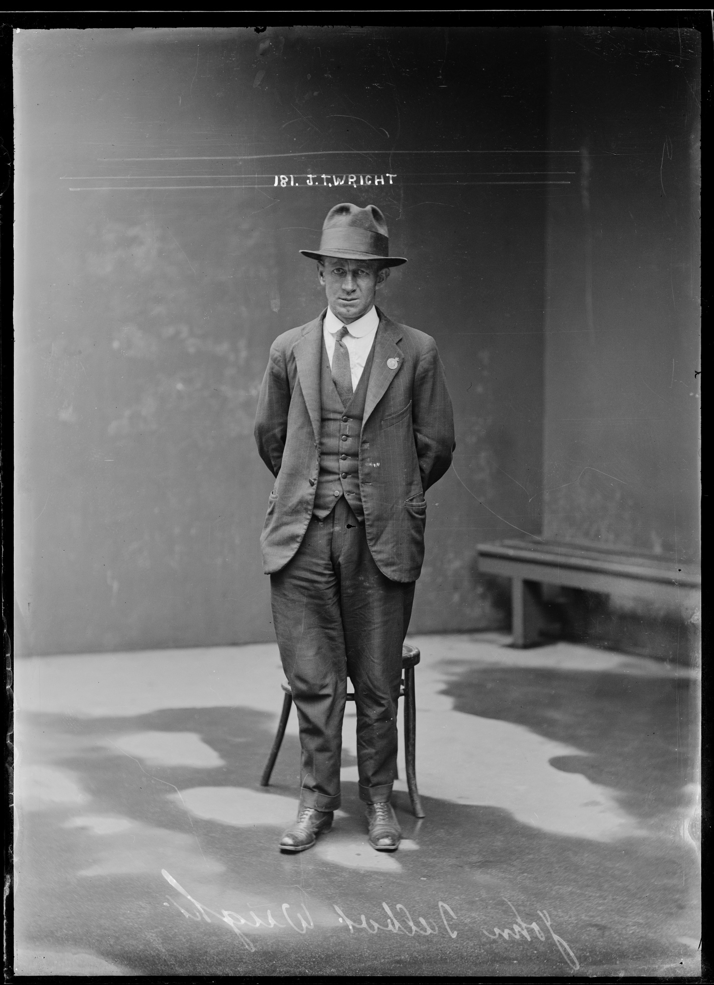 Full length police photo of man in suit and hat, standing in front of chair.