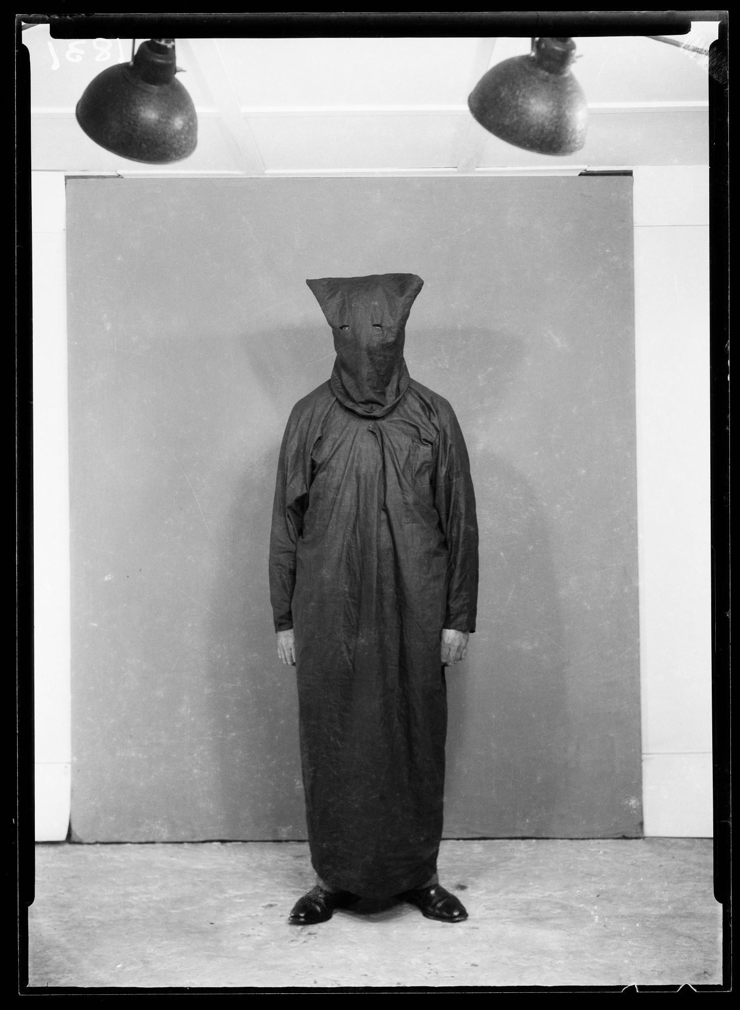 Man wearing dark robe and hooded mask, photographed in studio with overhead studio lights and backdrop shown in use.