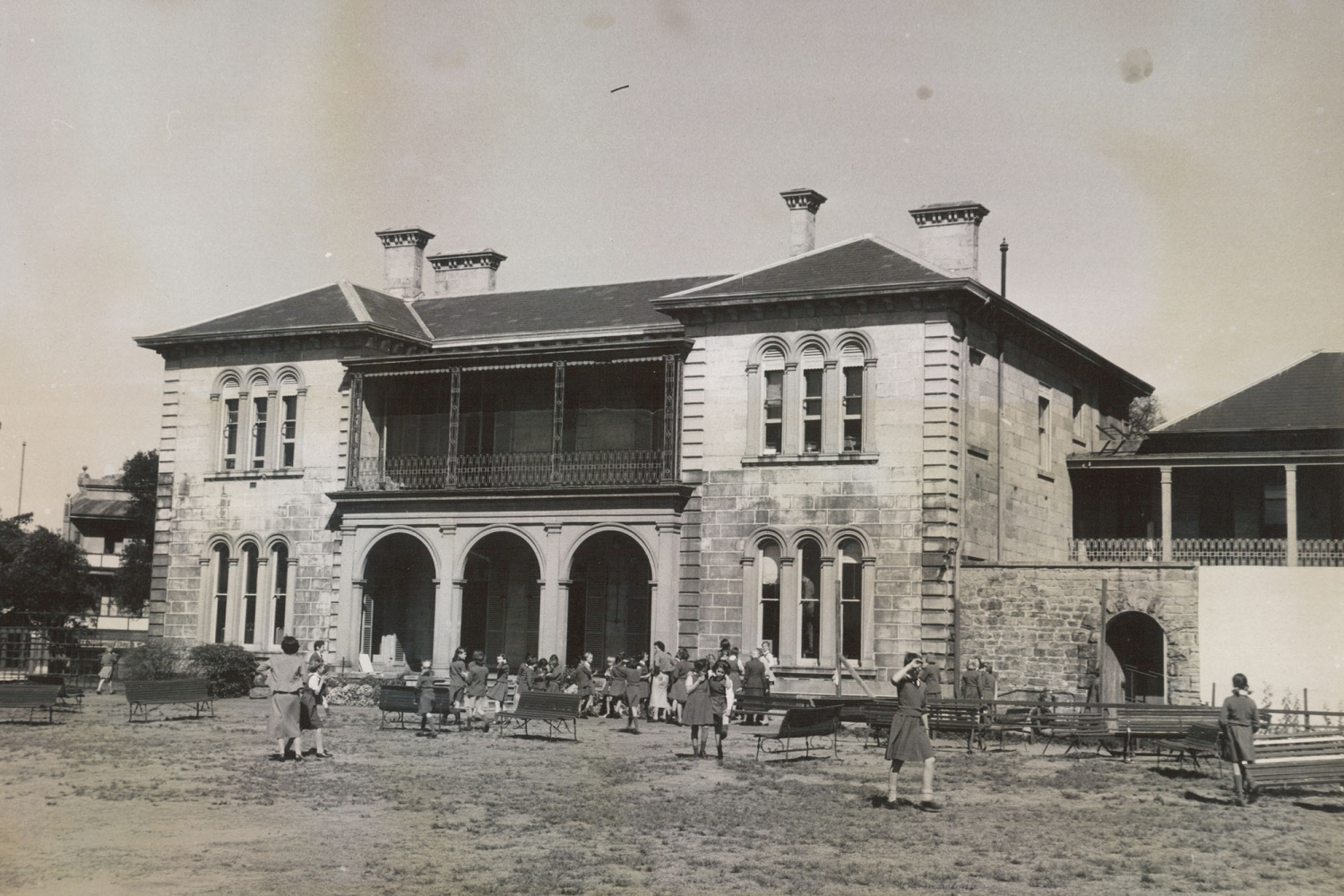 Black and white photo of two storey building with ground floor arches.