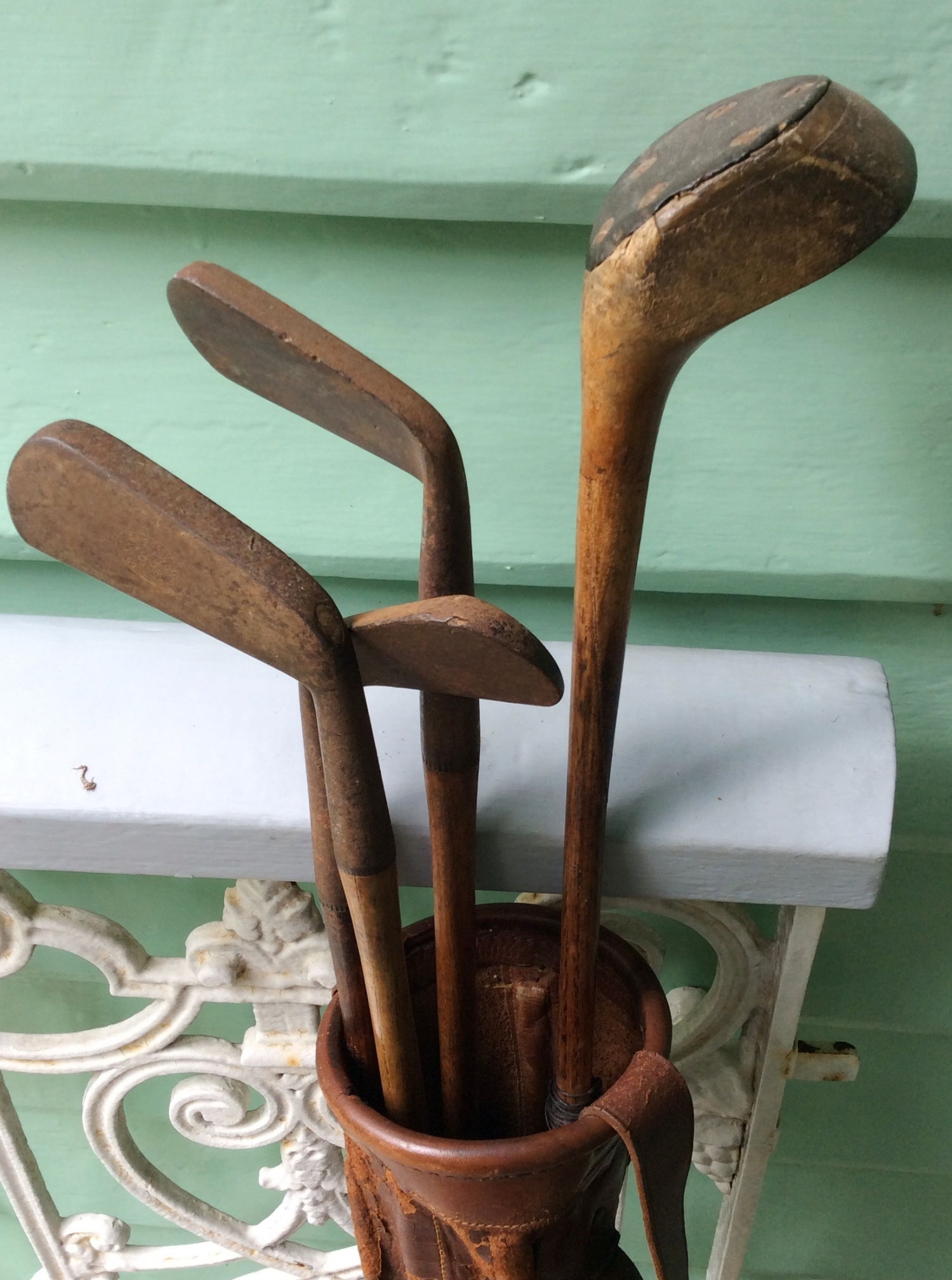 Closeup of four metal golf club heads.