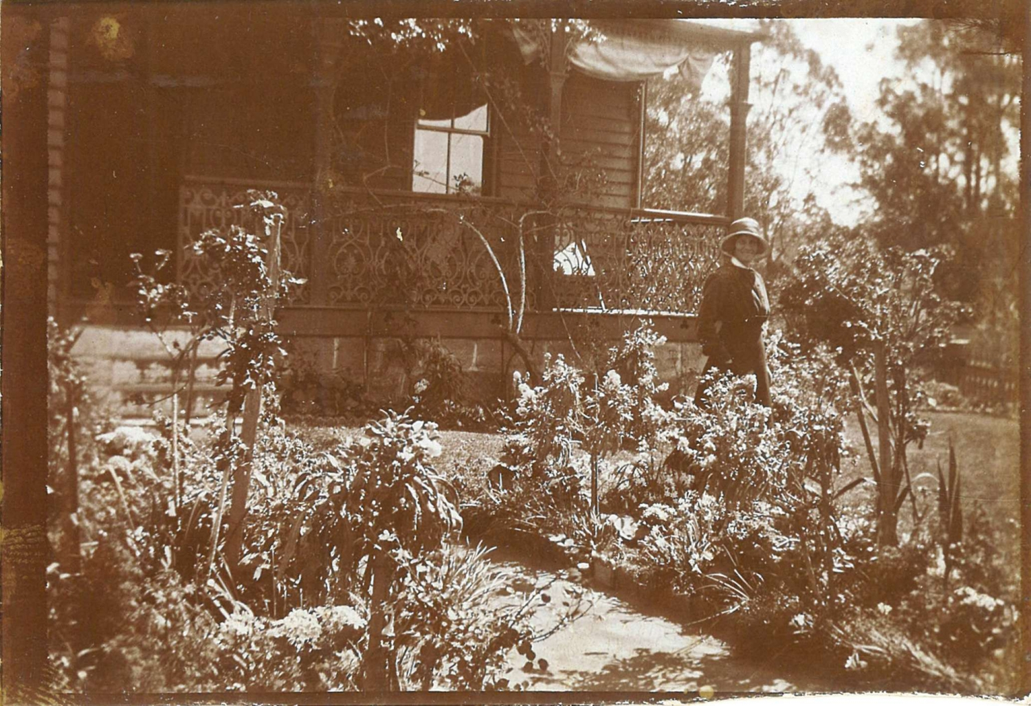 Black and white photo of figure in garden in front of house.