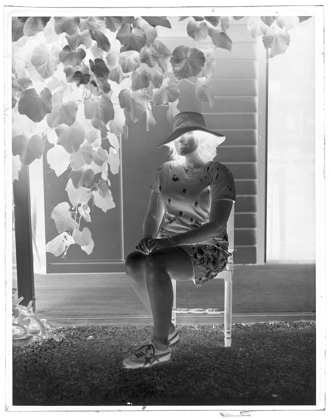 Black and white negative of woman sitting on chair in garden.