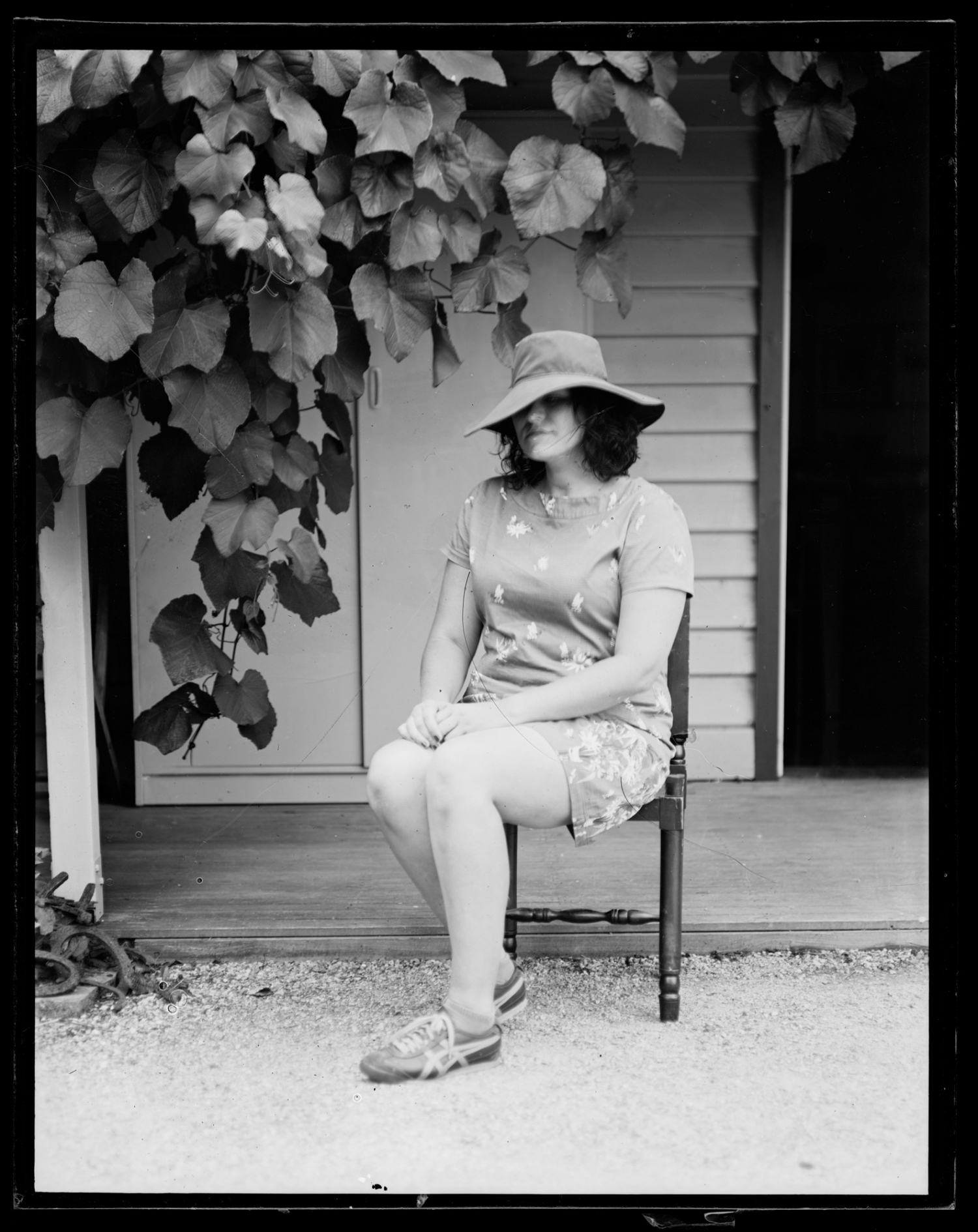 Black and white photo of woman sitting on chair in garden.