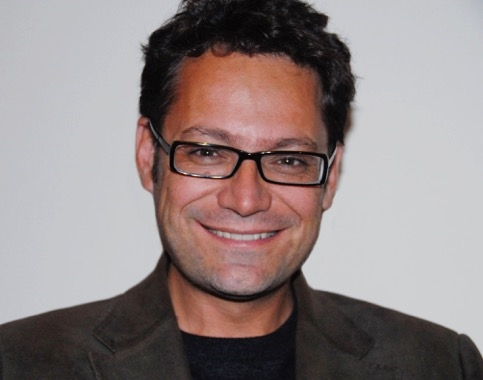 Head shot of man with curly hair and glasses.