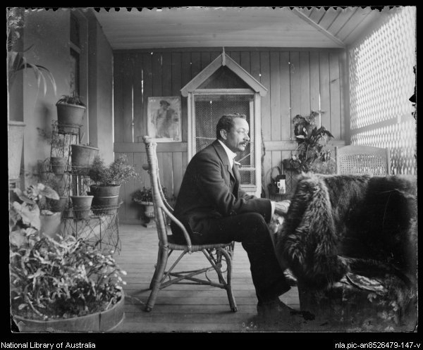 A man sits on the verandah surrounded by potted plants