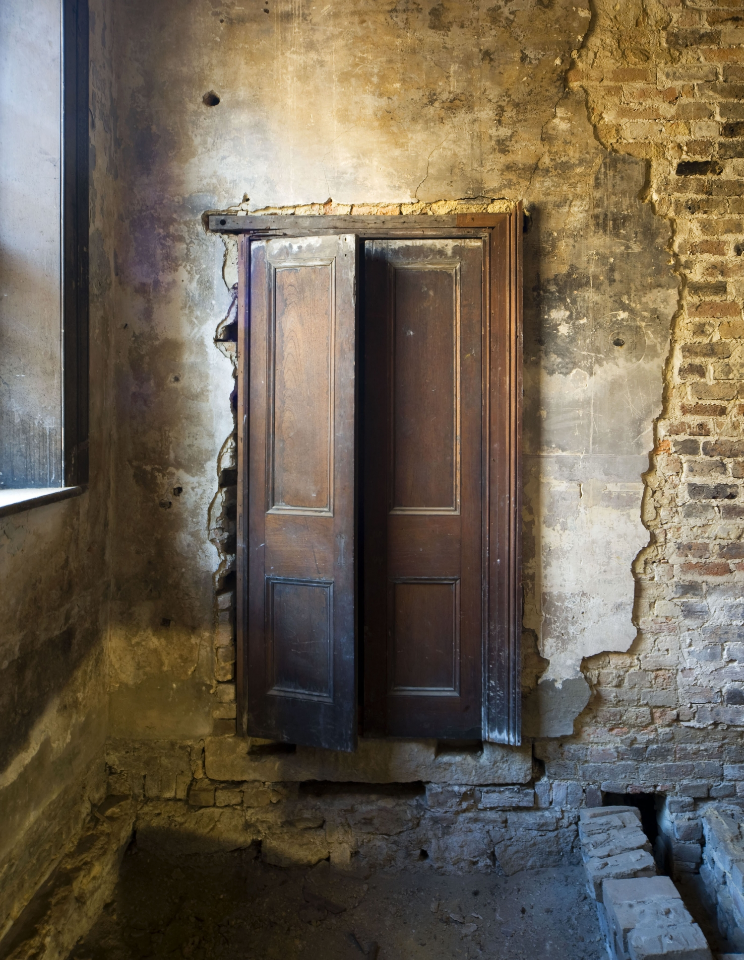 Old double doors preserved in an original and deteriorated brick wall with arched window to the left, exposed earth below and ceiling boards above.
