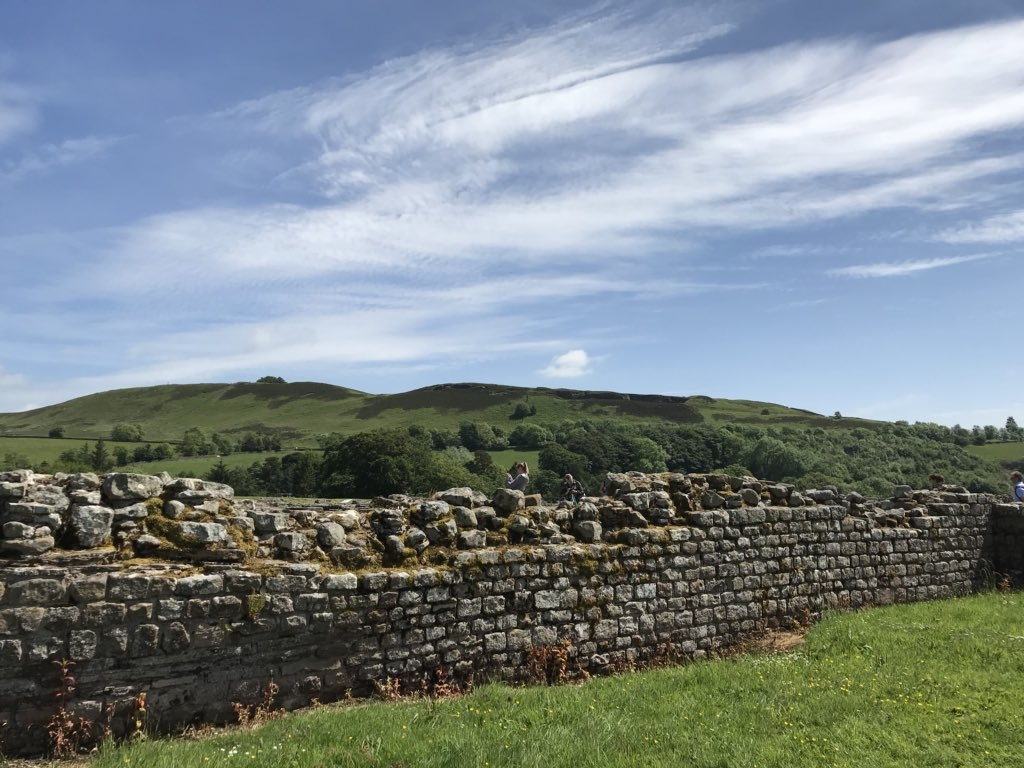Section of ancient stone wall with green fields in background.