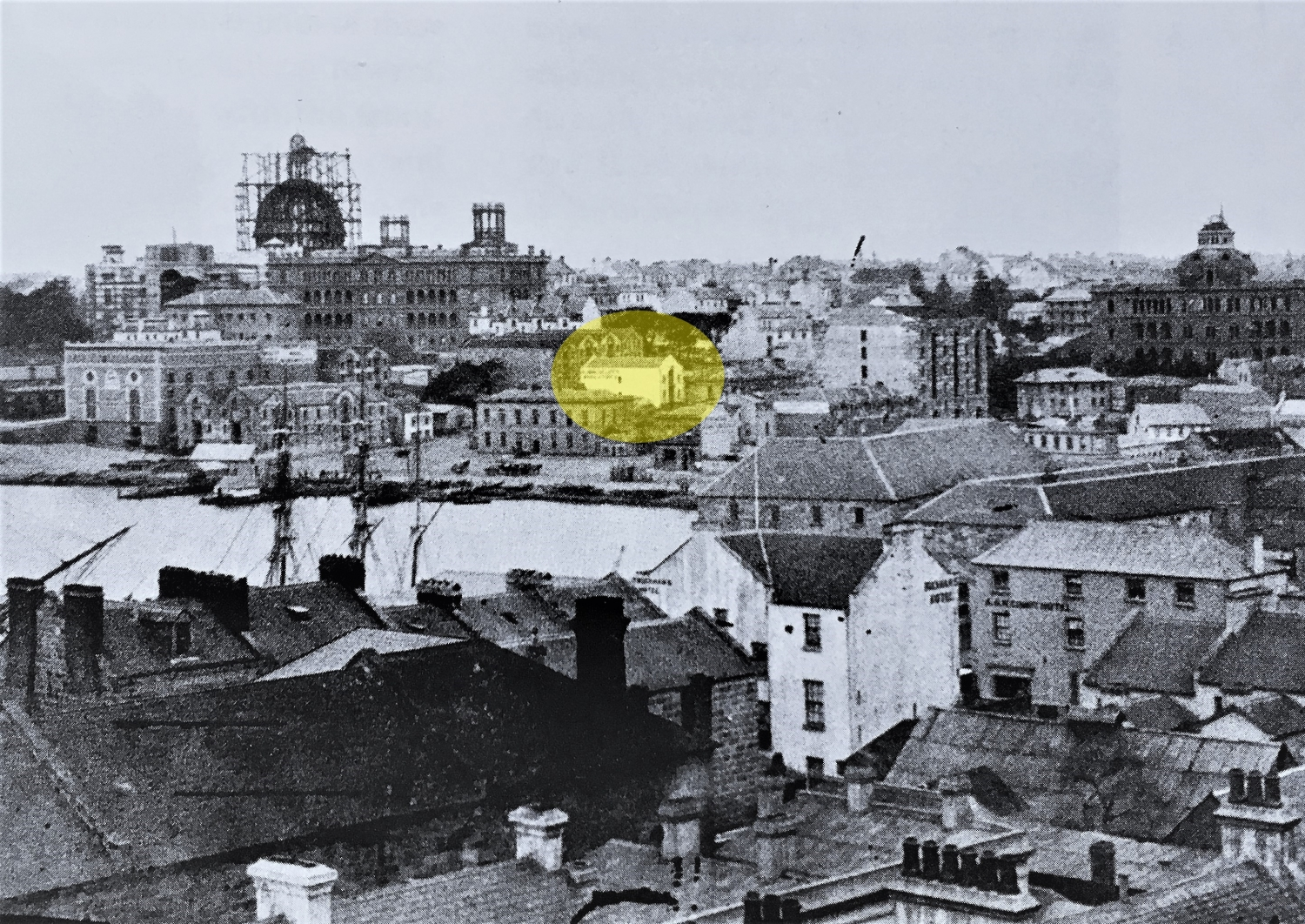 Black and white view of cityscape with yellow highlight on woolstore building in centre of image.