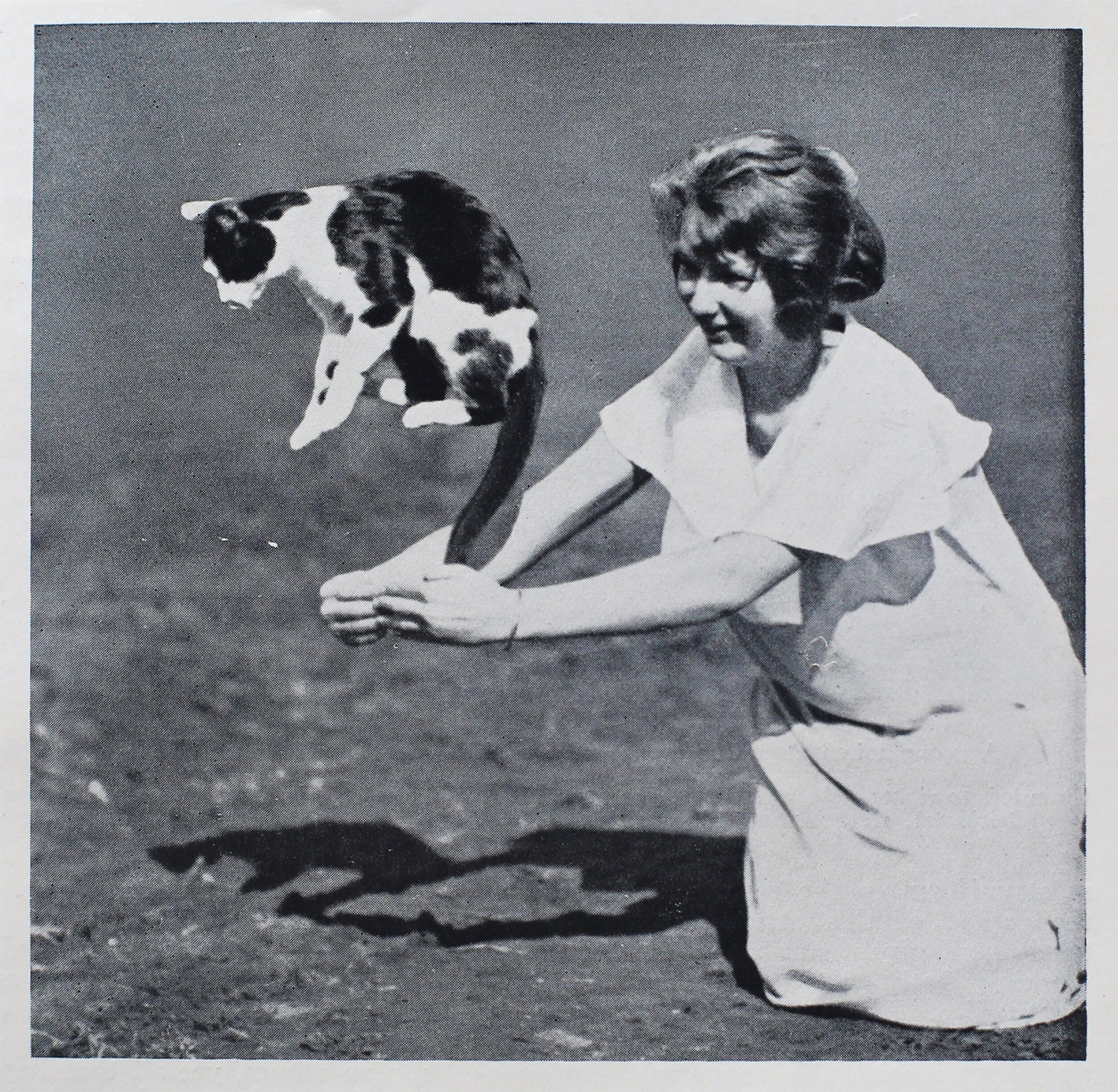 Black and white photo with white border showing cat jumping out of girl's arms.