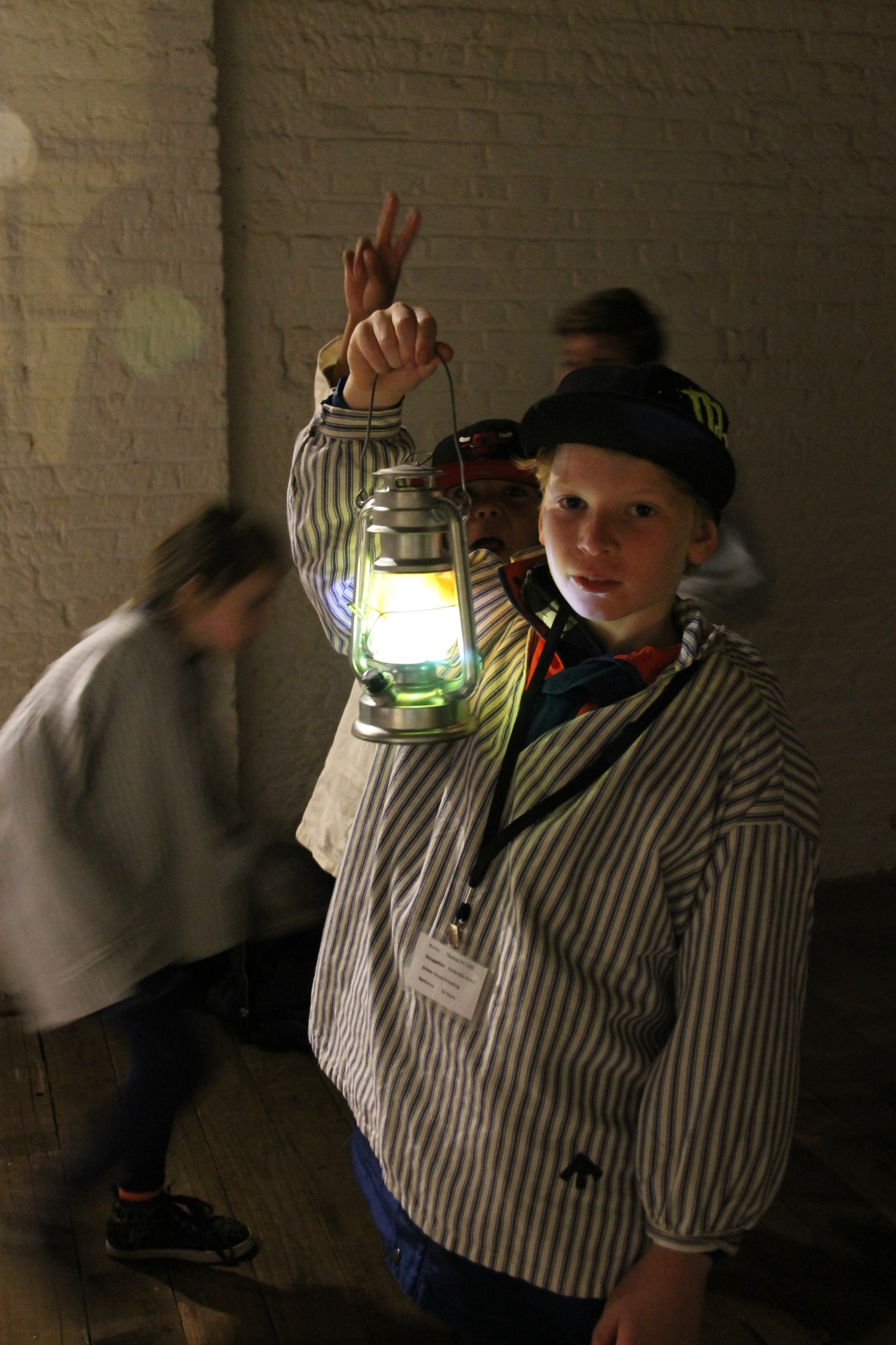 Boy dressed in convict clothes holding up lamp.