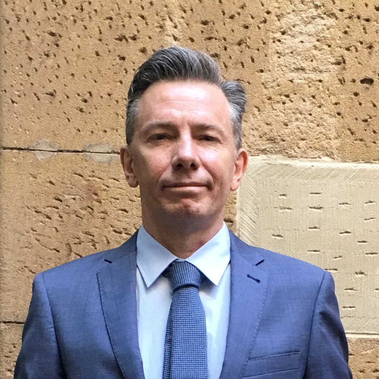 Man in blue suit in front of sandstone wall.