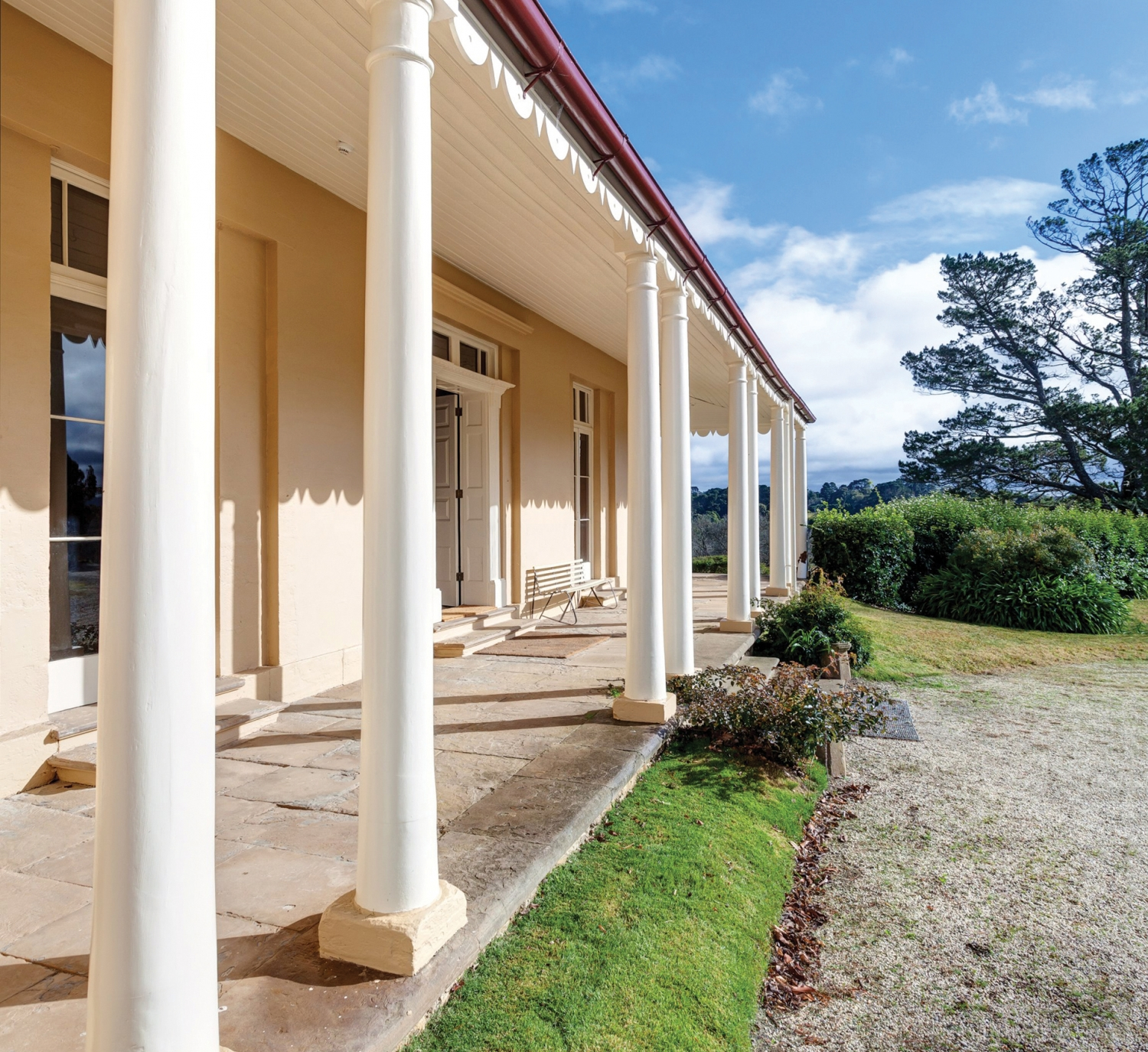View of front verandah and door with white columns, flagstones and garden beyond.