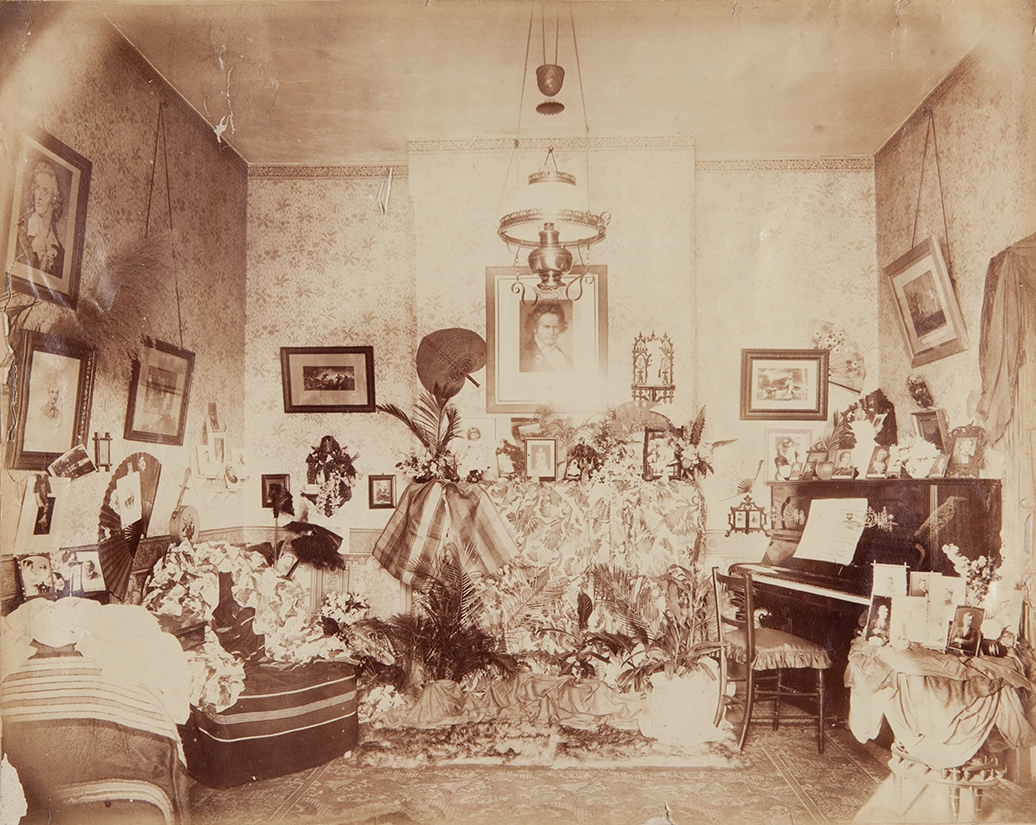Sepia toned photo of large cluttered room with piano to right.
