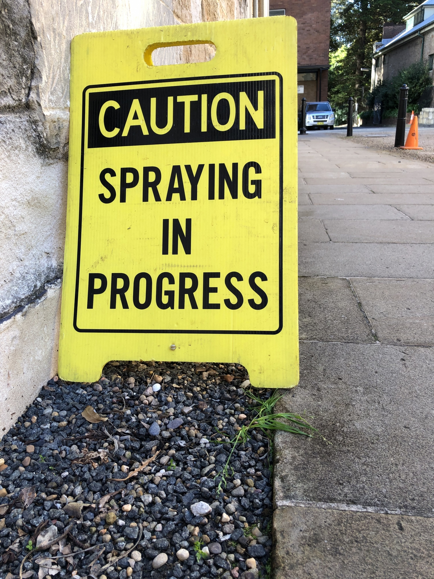 "a yellow and black sign reads ""caution spraying in progress"" anlongside a sandstone wall and path"