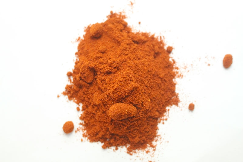 A pile of orange spice powder on white background.