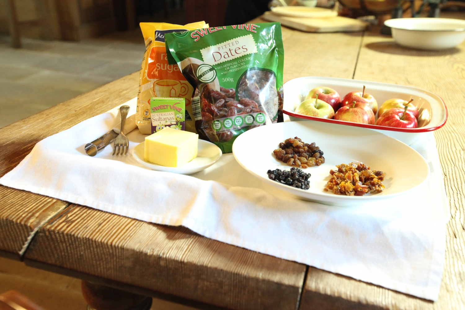 Close up of ingredients and equipment on wooden table: packet of raw sugar, packet of dates, baking tray with 6 apples, plate with sultanas and other dried fruit, slab of butter, apple corer and table fork.