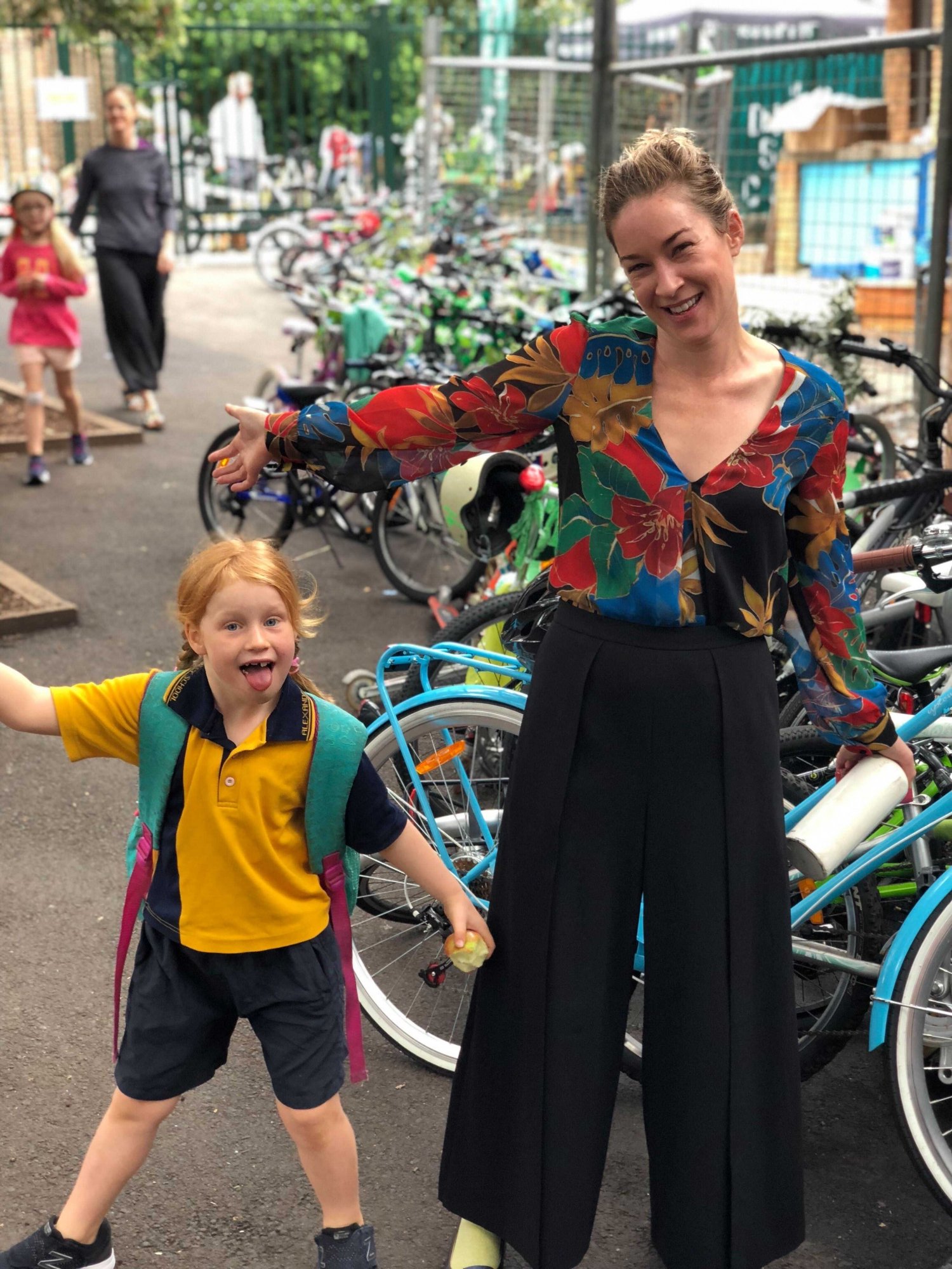 Woman and child in colourful clothes in school yard with bicycles.