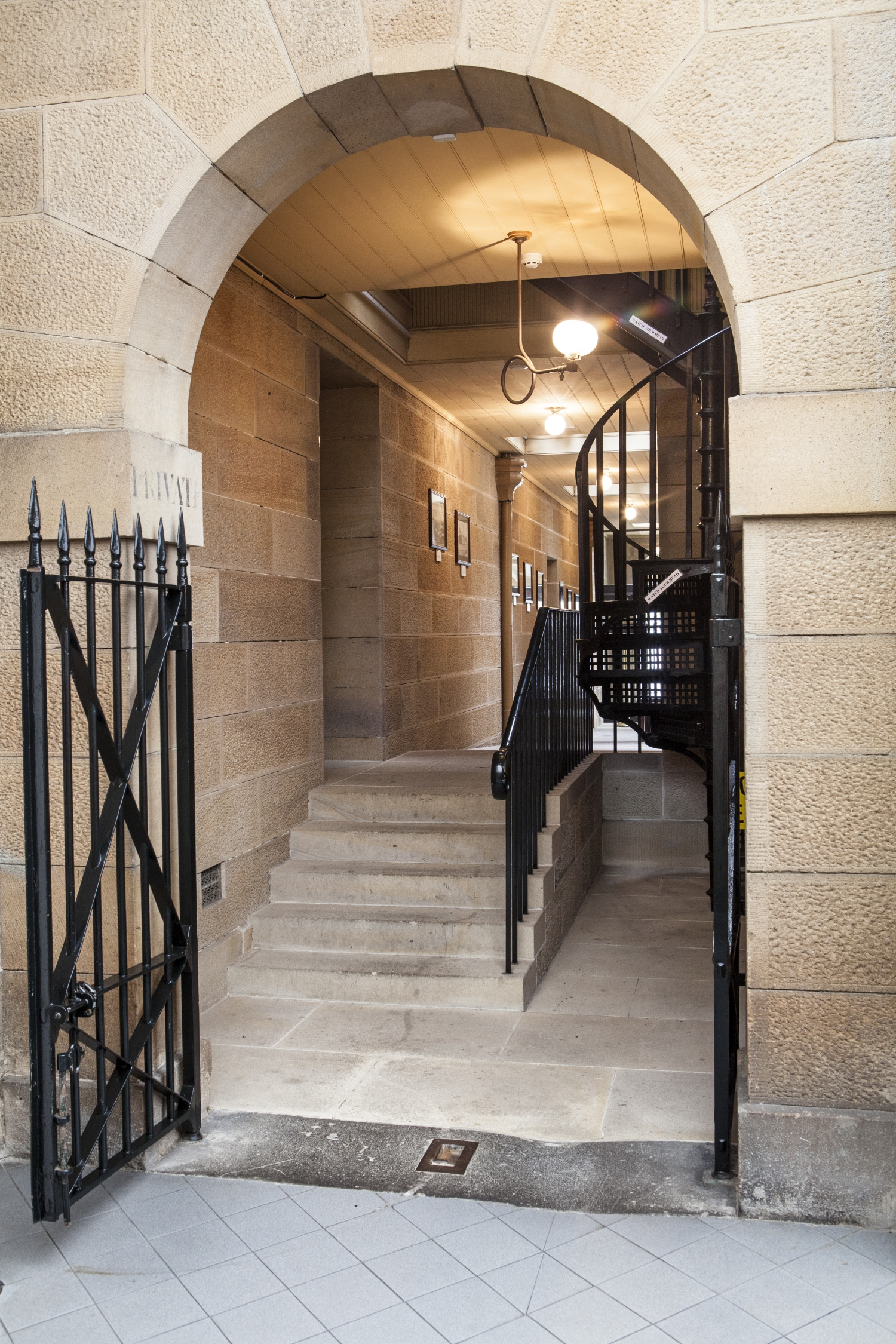 Black-painted metal gate and archway leading into sandstone corridor with steps and spiral staircase visible.