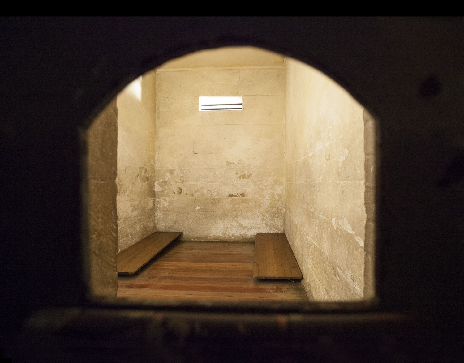View through door hatch into stark holding cells at the Justice and Police Museum, showing 2 timber platform beds.