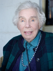 Portrait of elderly woman wearing blue and purple clothes, with grey hair.