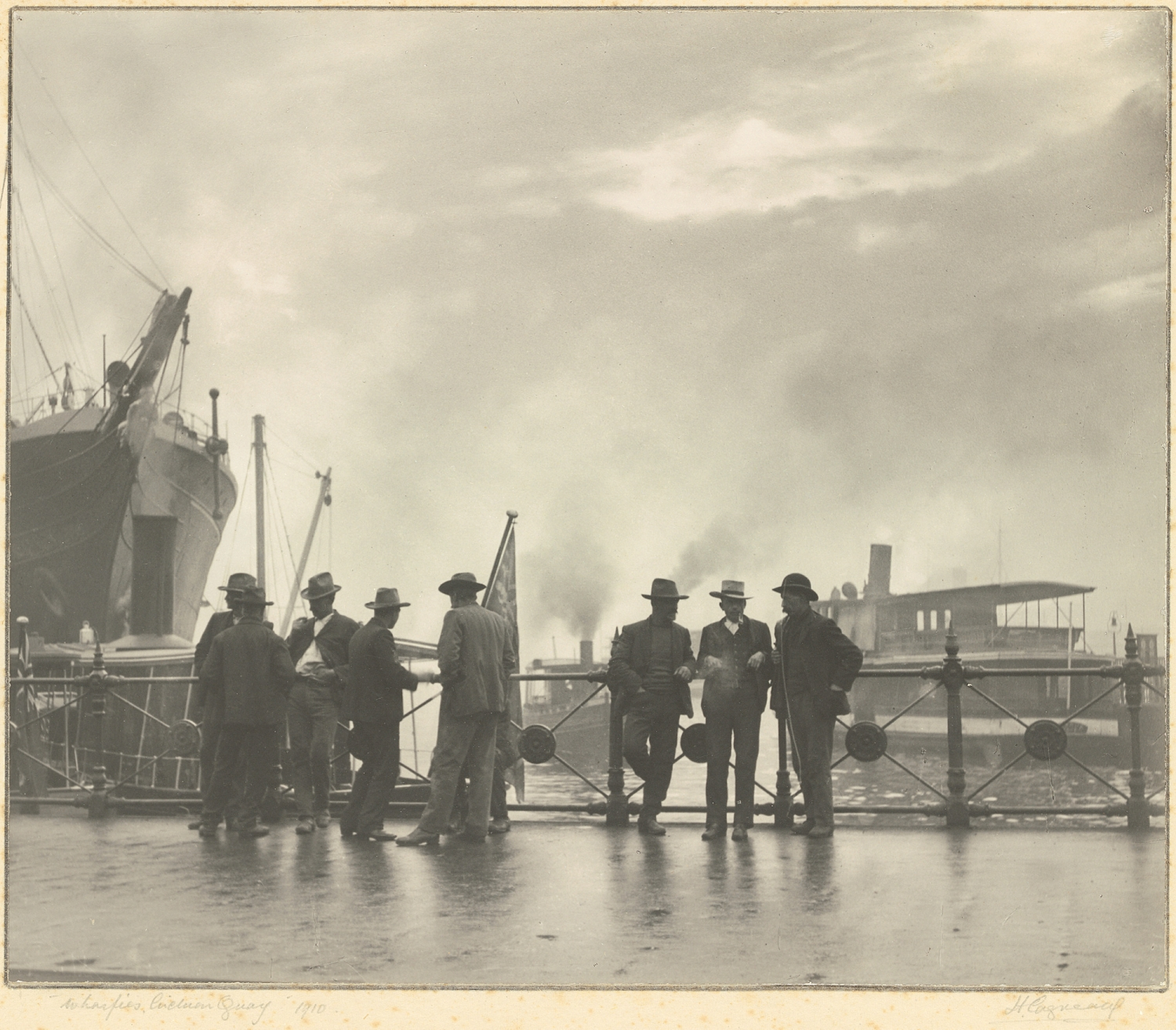 Group of eight men in hats standing in front of harbour scene with boats in background.
