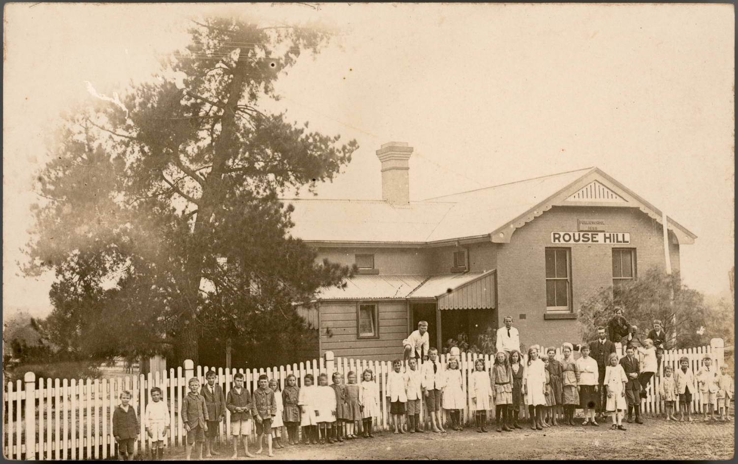 Sepia toned photo of group of children outside front fence of school building.