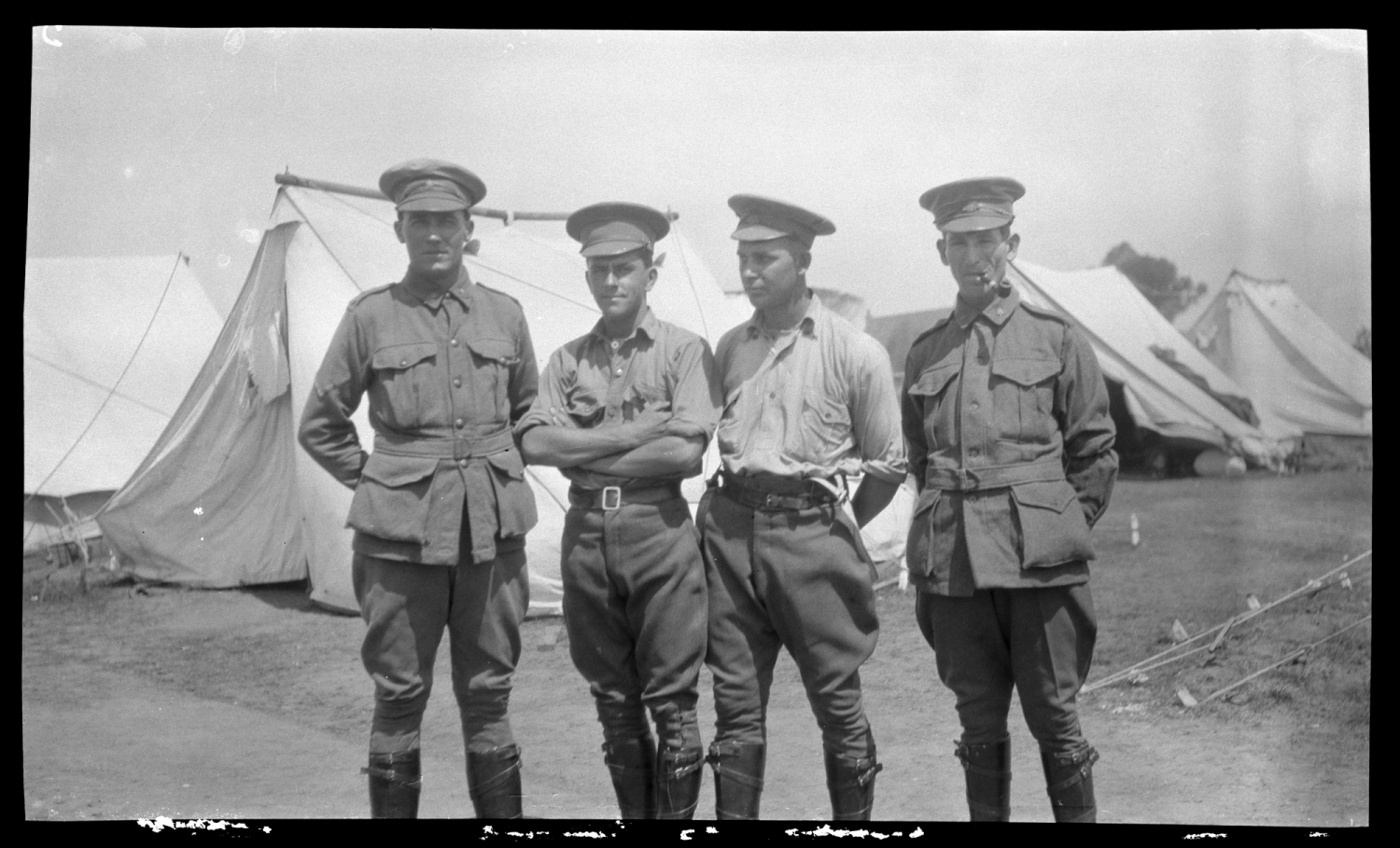 Four men in uniform standing outdoors with tents in background.