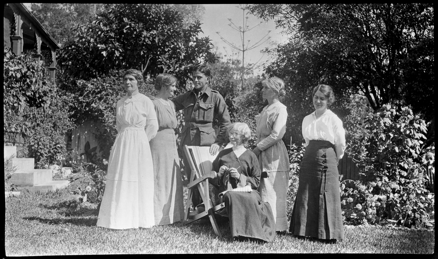 Group of women and one man standing around one seated woman in chair.