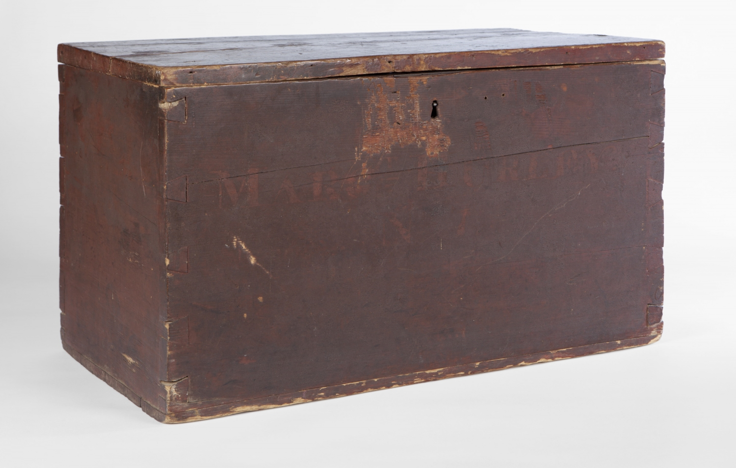 Plain scuffed dark brown wooden box with name 'Hurley' faintly visible on front.