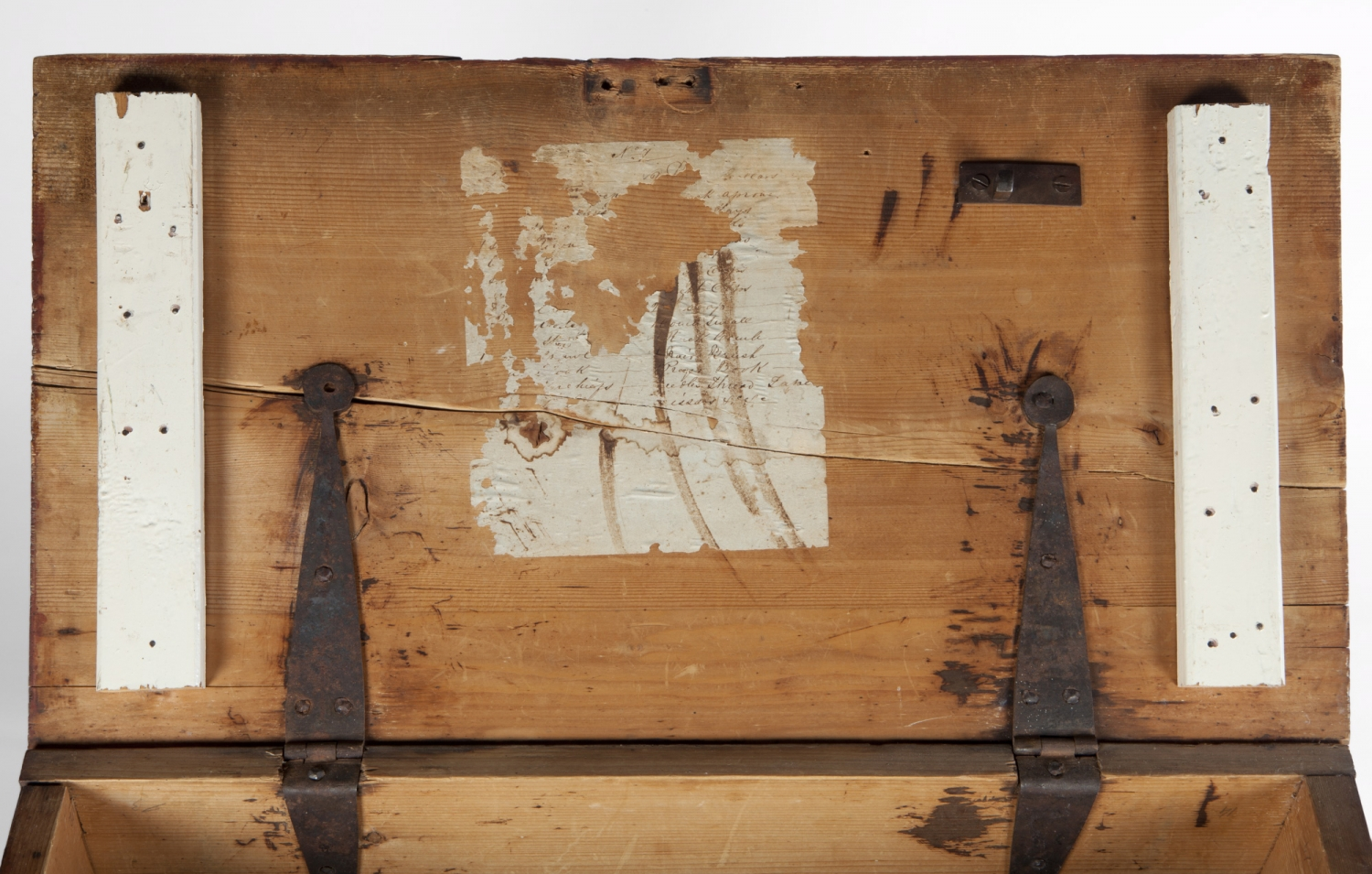 Closeup of inside lid of box showing hinges and patch where something has been scraped off.