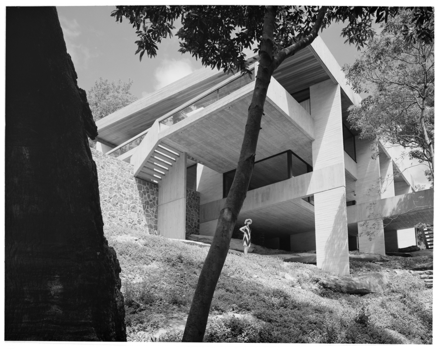 Black and white photo of exterior of modernist house with figure standing underneath it.