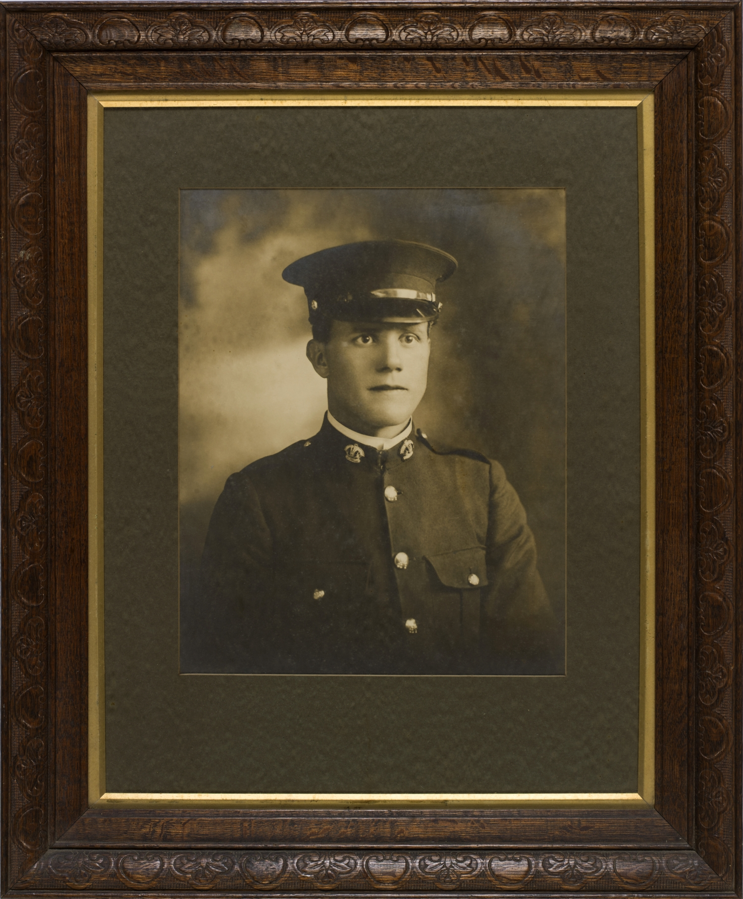 Sepia toned photograph of man in uniform with cap in brown leather frame.