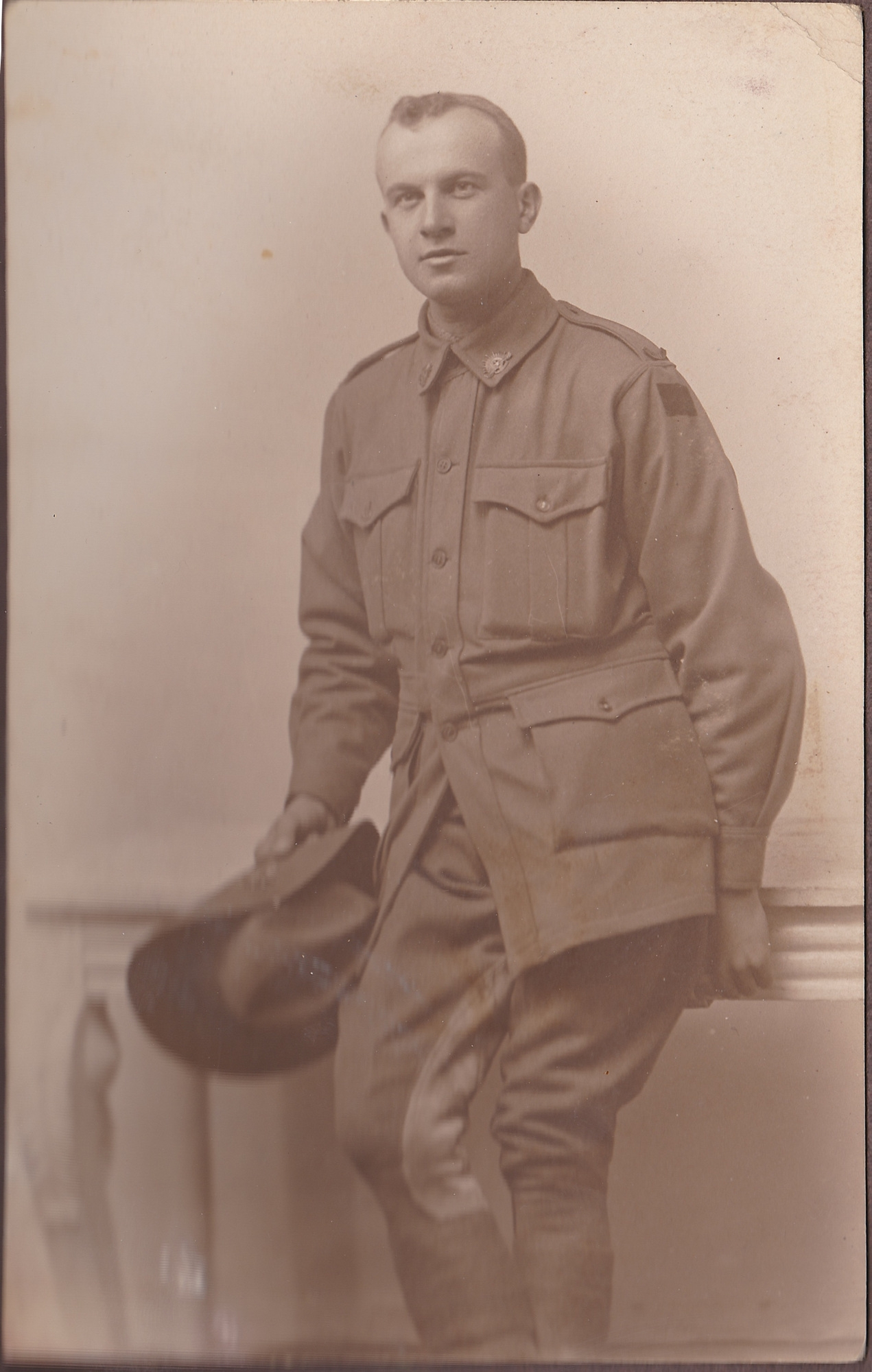 Man in uniform leaning on low wall.