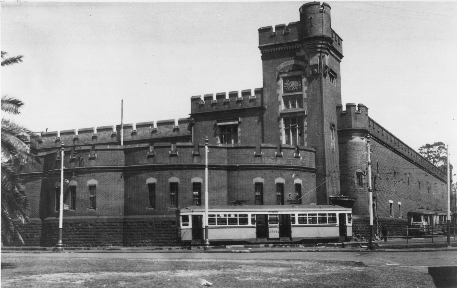 Black and white photograph of a building with a tram in the foreground.
