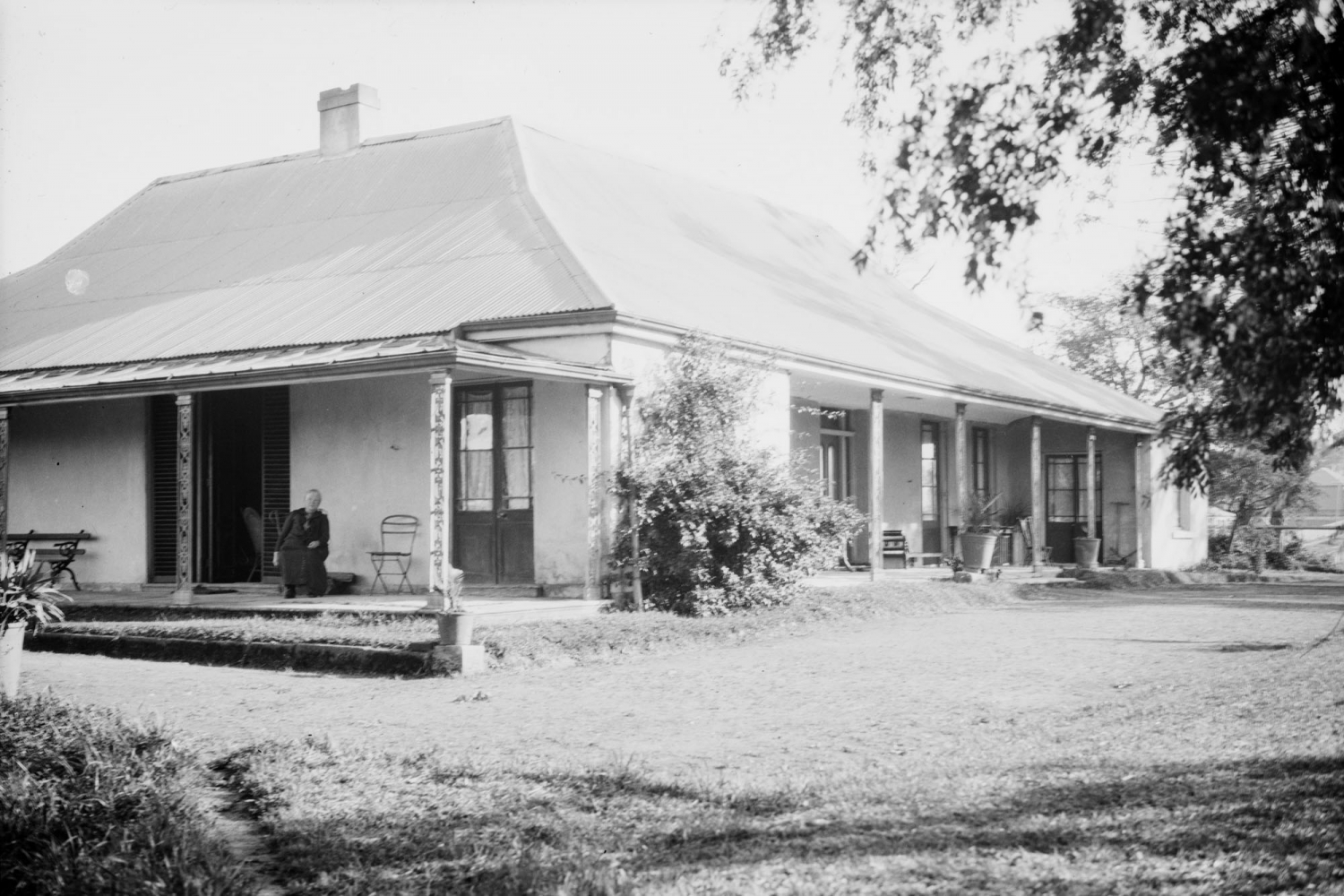 Black and white photo of person seated on verandah of single storey farm house.