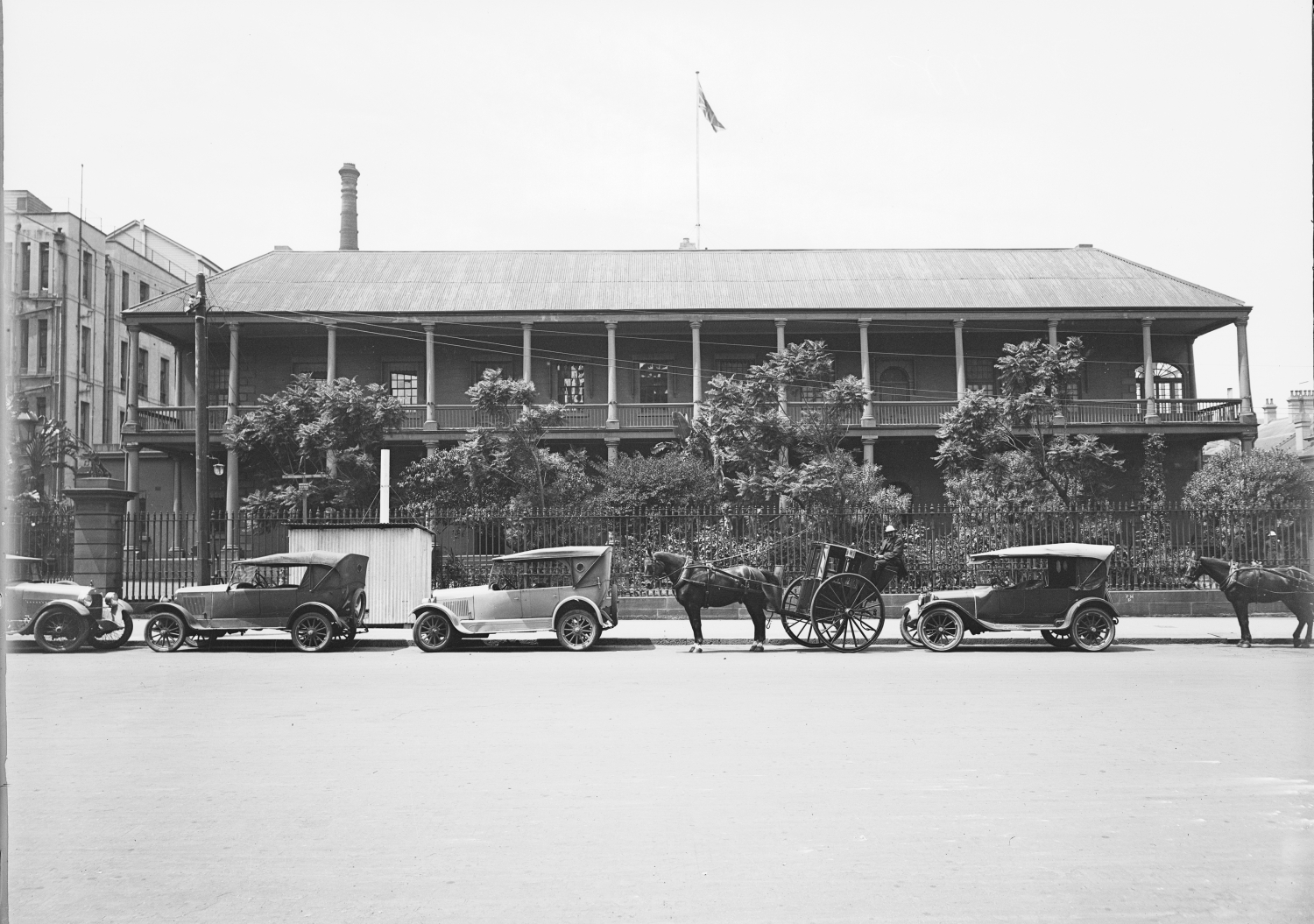 Black and white photo of vehicles and horses outside two storeyed colonial building.