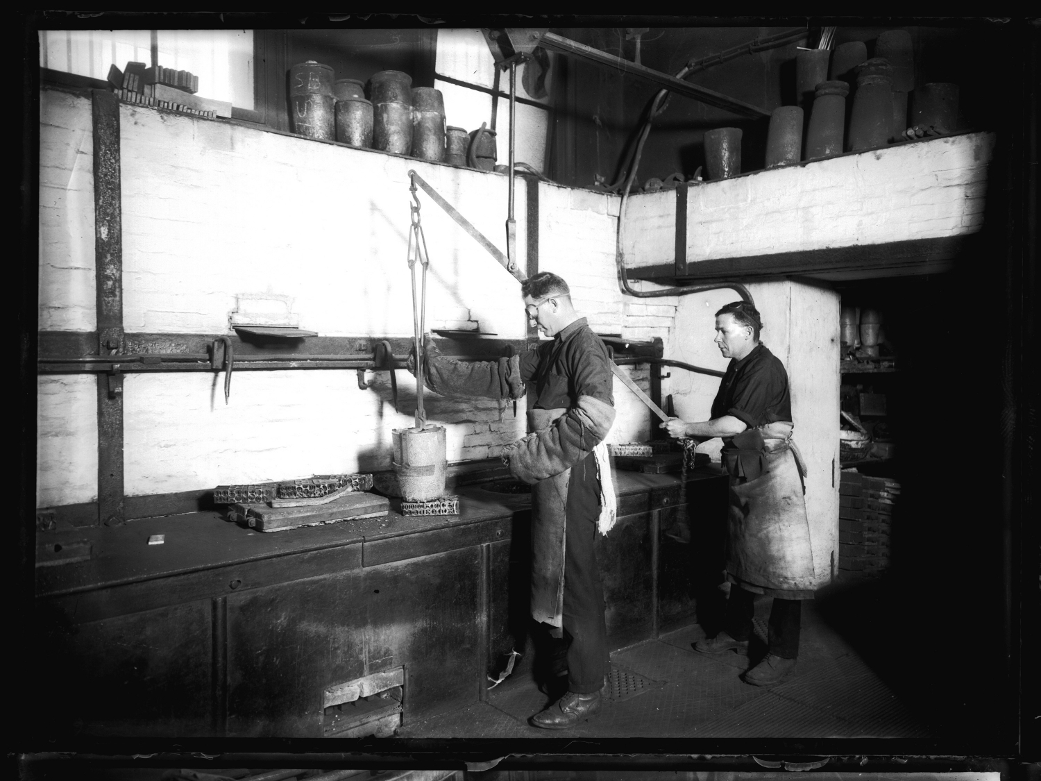 Black and white photo of two men at bench working.