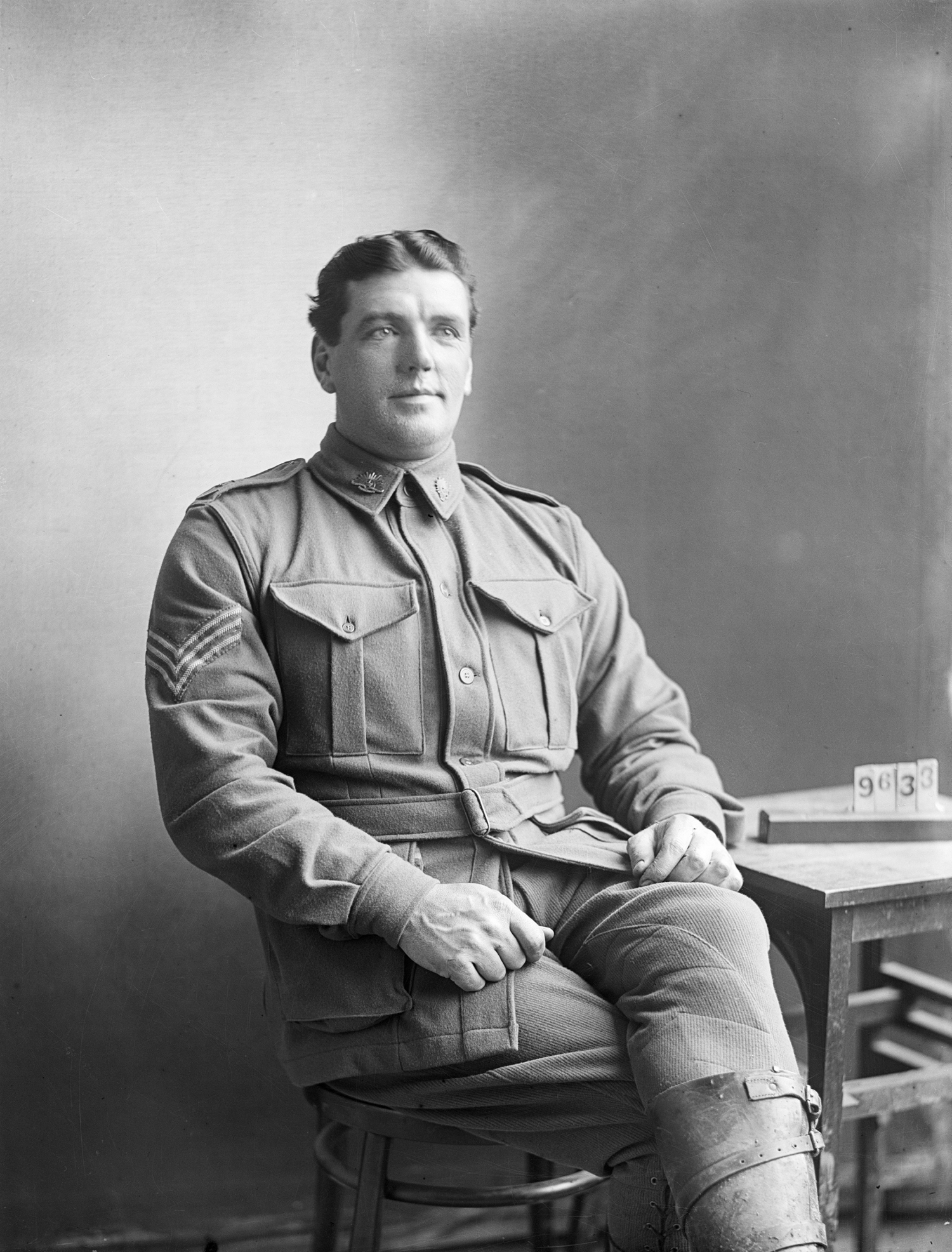 Black and white illustration of a seated man in uniform.
