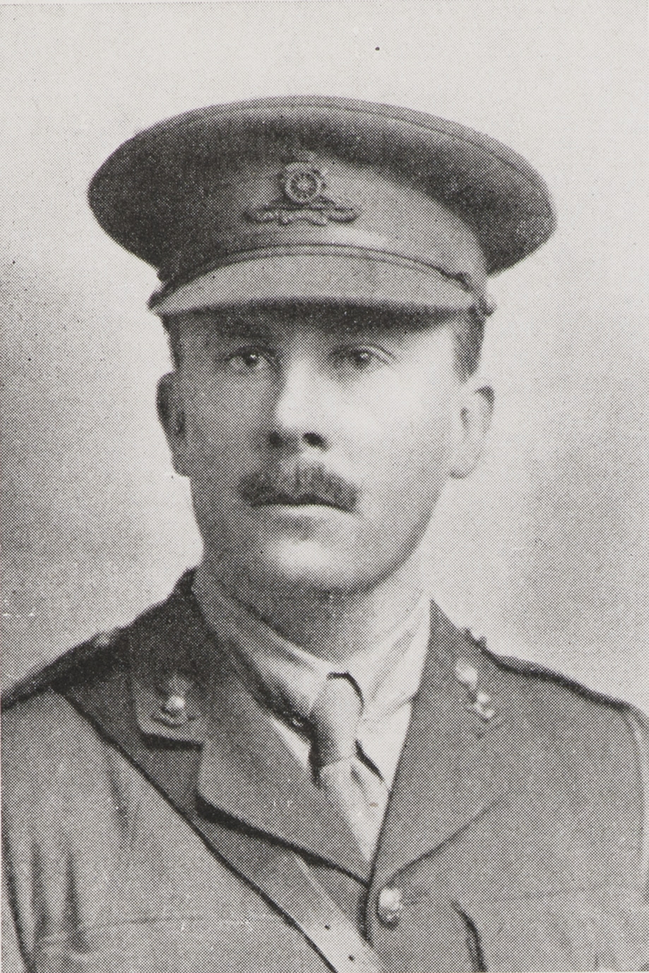 Black and white portrait of man in uniform with moustache.